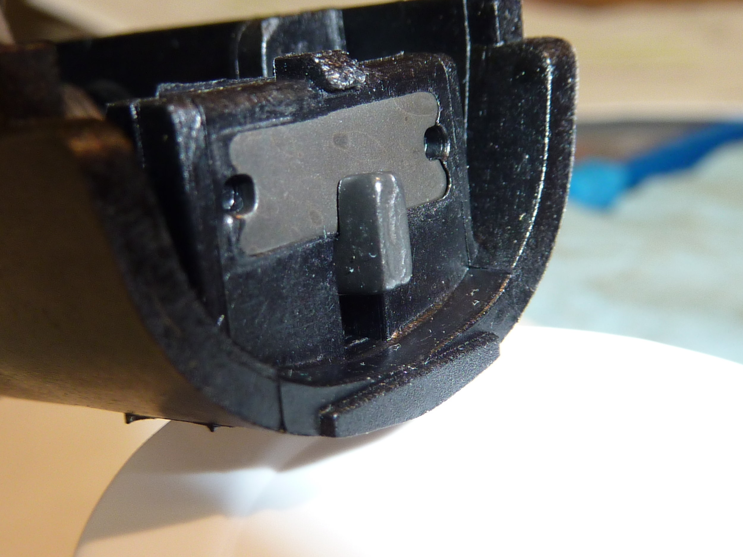 Note that the little hook is in the fully engaged position. Now, screw in the trigger adjustment screw until it starts to contact the trigger housing body. This will take a little movement initially since the screw was deliberately pre-set to provide clearance between the screw and the housing to ease assembly (see above). As the screw contacts the trigger housing body the little hook will start to move down in its slot. Stop screw adjustment when the top of the hook is level with the bottom of the metal plate, as below.