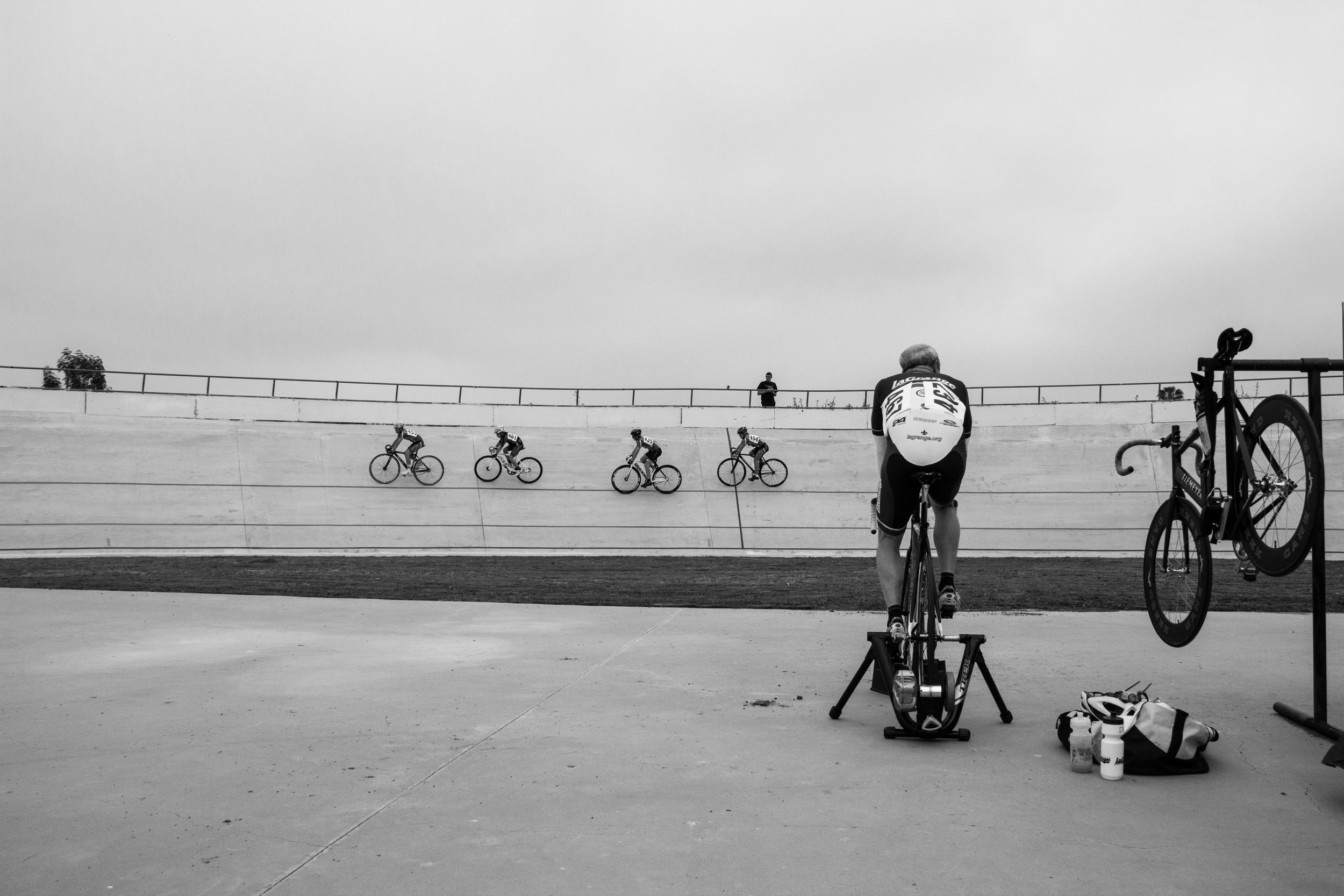 7. A lone rider warms up while watching the races at the Encino Velodrome on a grey day.
