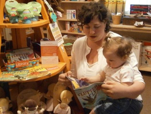 PHOTO CAPTION: Amanda Hummel, owner of The Bee's Knees, and daughter Inez Solomon, are both fans of the INDESTRUCTIBLES, a series of non-toxic, chew-proof, rip-proof, 100% washable books for babies. Proceeds from the sale of these books over the course of the Summer will be donated to the Campaign for the Hudson Area Library. The promotion, including bright orange signs and handouts for customers, is an effort to spread the word about the Hudson Area Library's fundraising campaign. Three other retailers are also part of this promotion – Olde Hudson, TK Home & Garden and Verdigris Tea & Chocolate Bar.