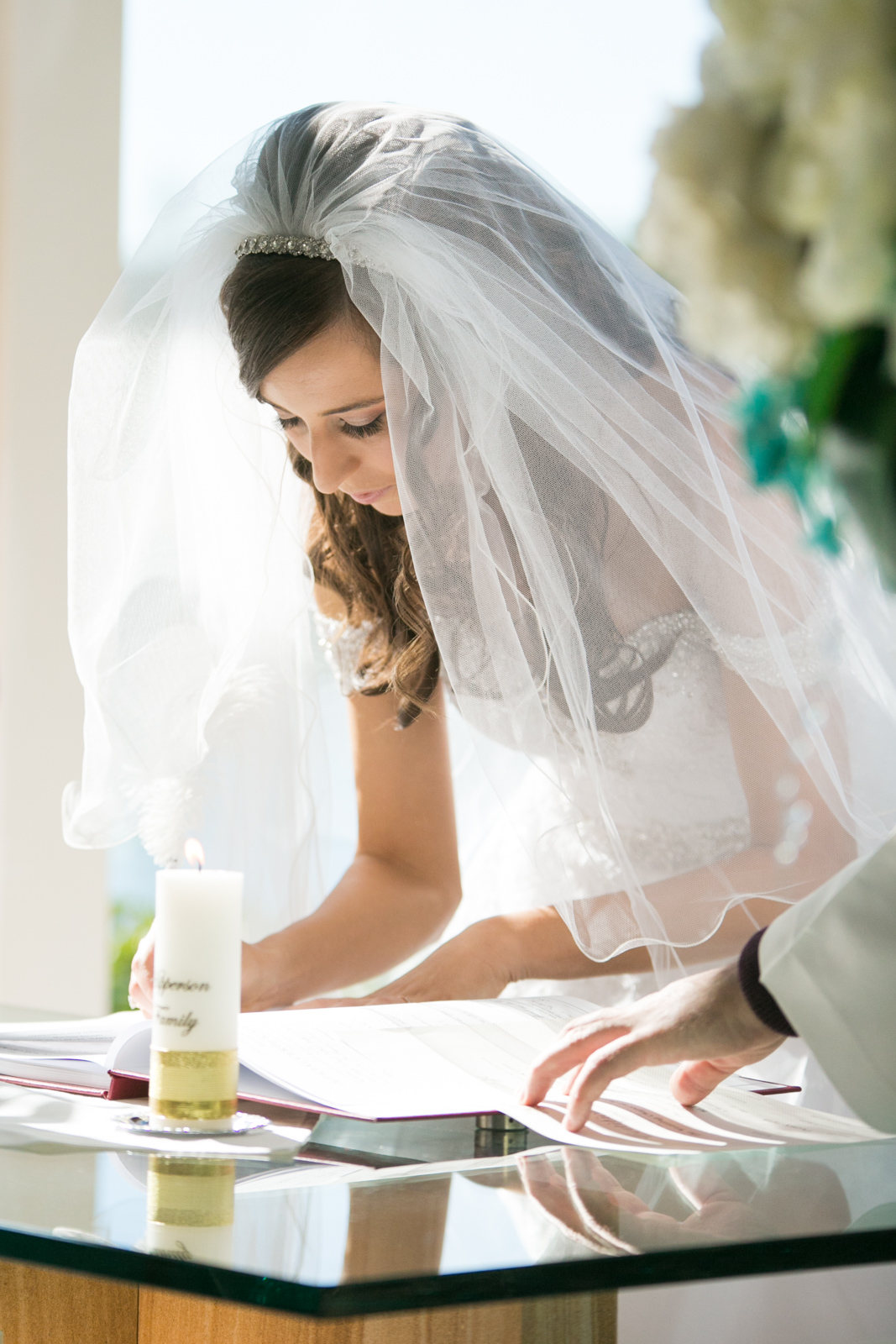 A open veil shot as Bianca signs the Marriage certificate