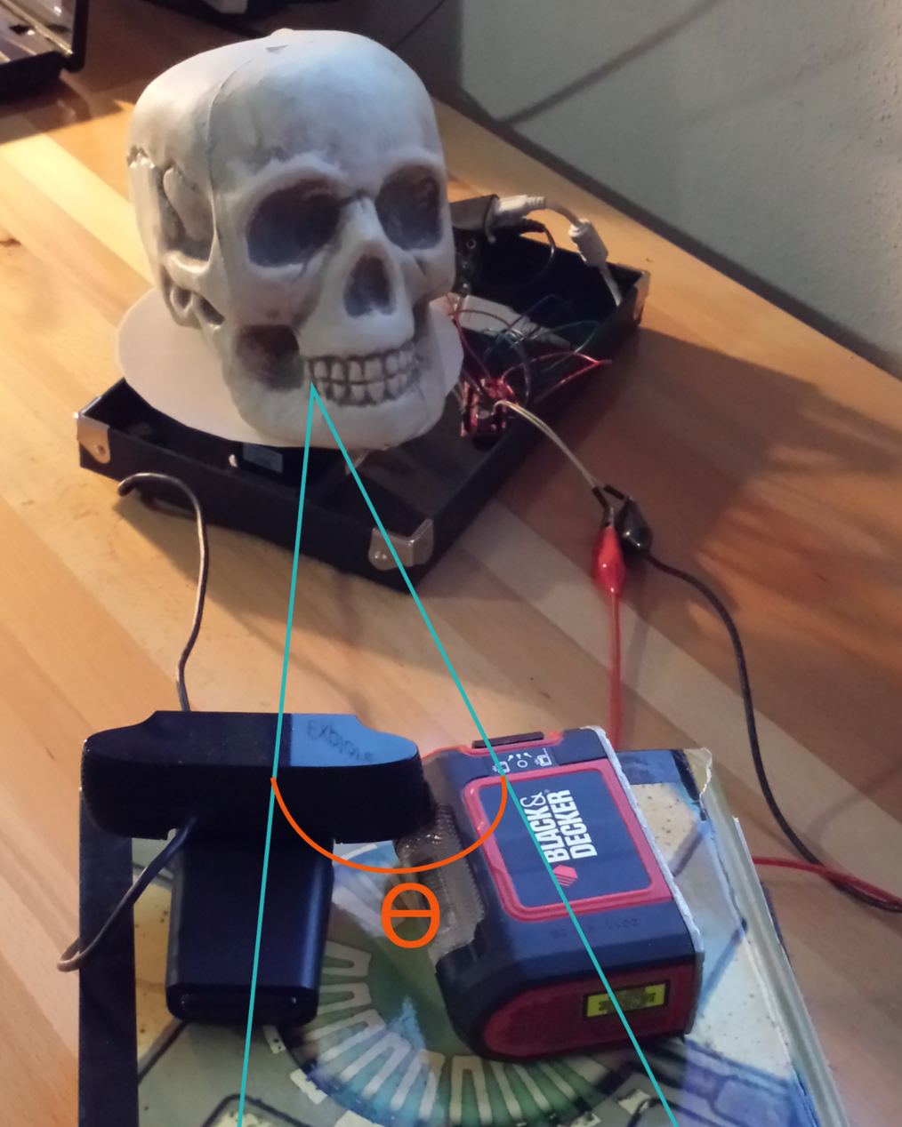 The arrangement of hardware components. The embedded linux device, stepper motor driver, and stepper motor are placed in an upside-down box lid, and the camera/laser are resting on a stack of textbooks. Choose a camera/laser height which allows the laser to best fill the cavities of the device being scanned. Ө (Theta) defines the angle between the center of the camera's field of vision and the plane of the laser.