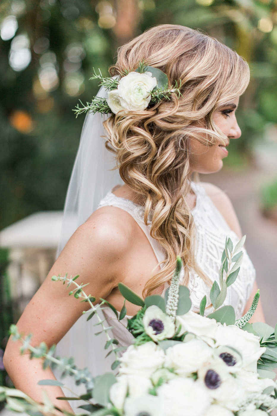 curled faux braided hairstyle on bride with flowers