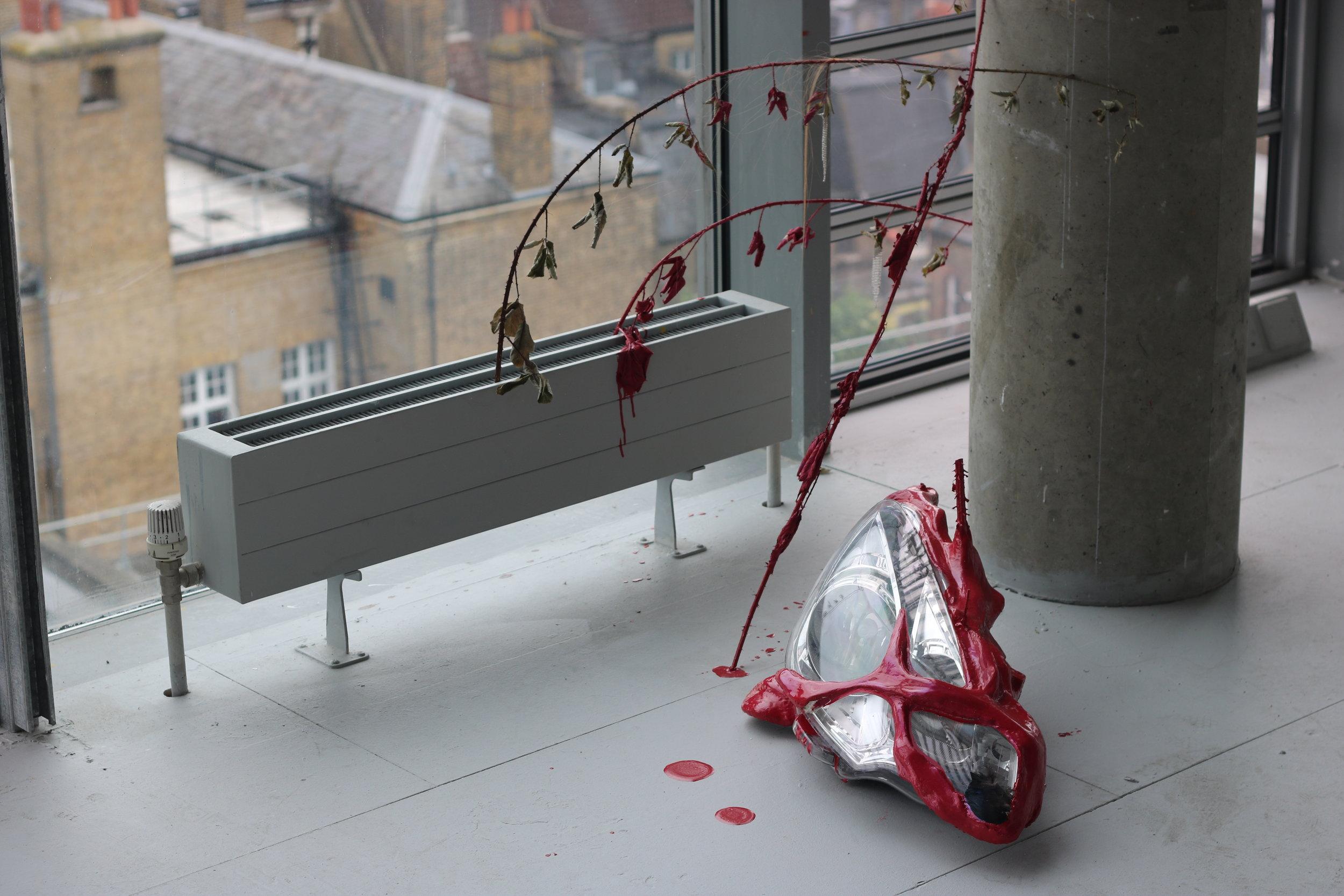 'changeling', car headlight, clay, bird wing, human hair, blackberry branches, rhinestone earrings, ferrari red automotive paint
