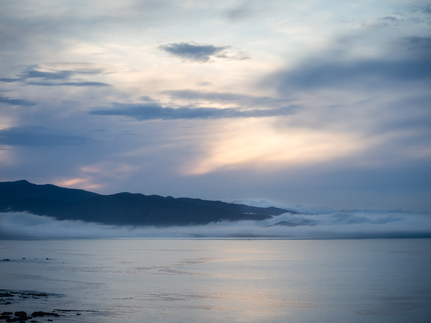 Looking toward the headland extending from the Orongorongo range, on Wellington's south coast.  The light of sunrise is reflected in the calm water, but the lighthouse beyond is obscured by the low lying cloud.