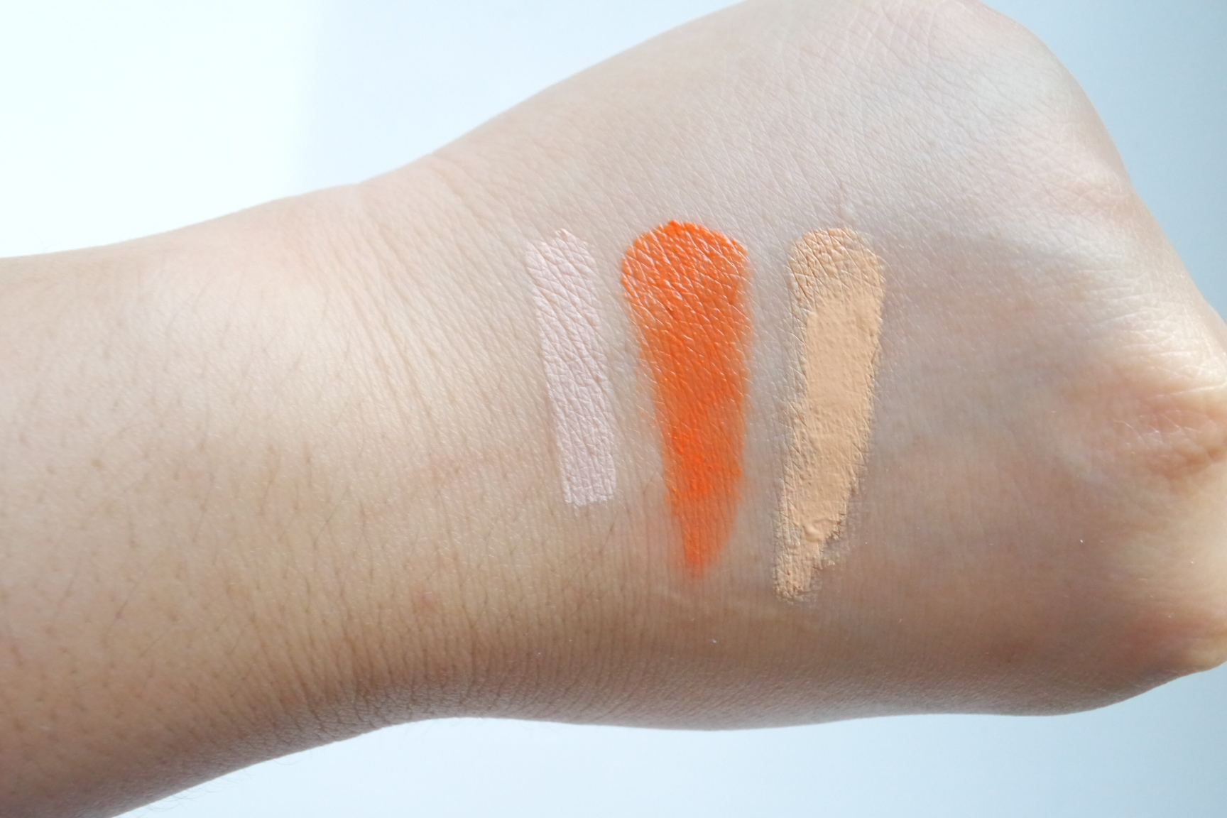 Swatches, from left: elf Eyelid Primer in Sheer, orange shade from Tony Moly Panda's Dream Dual Lip and Cheek Tint in Bubble Red, K-Palette Zero Kuma Concealer in 02