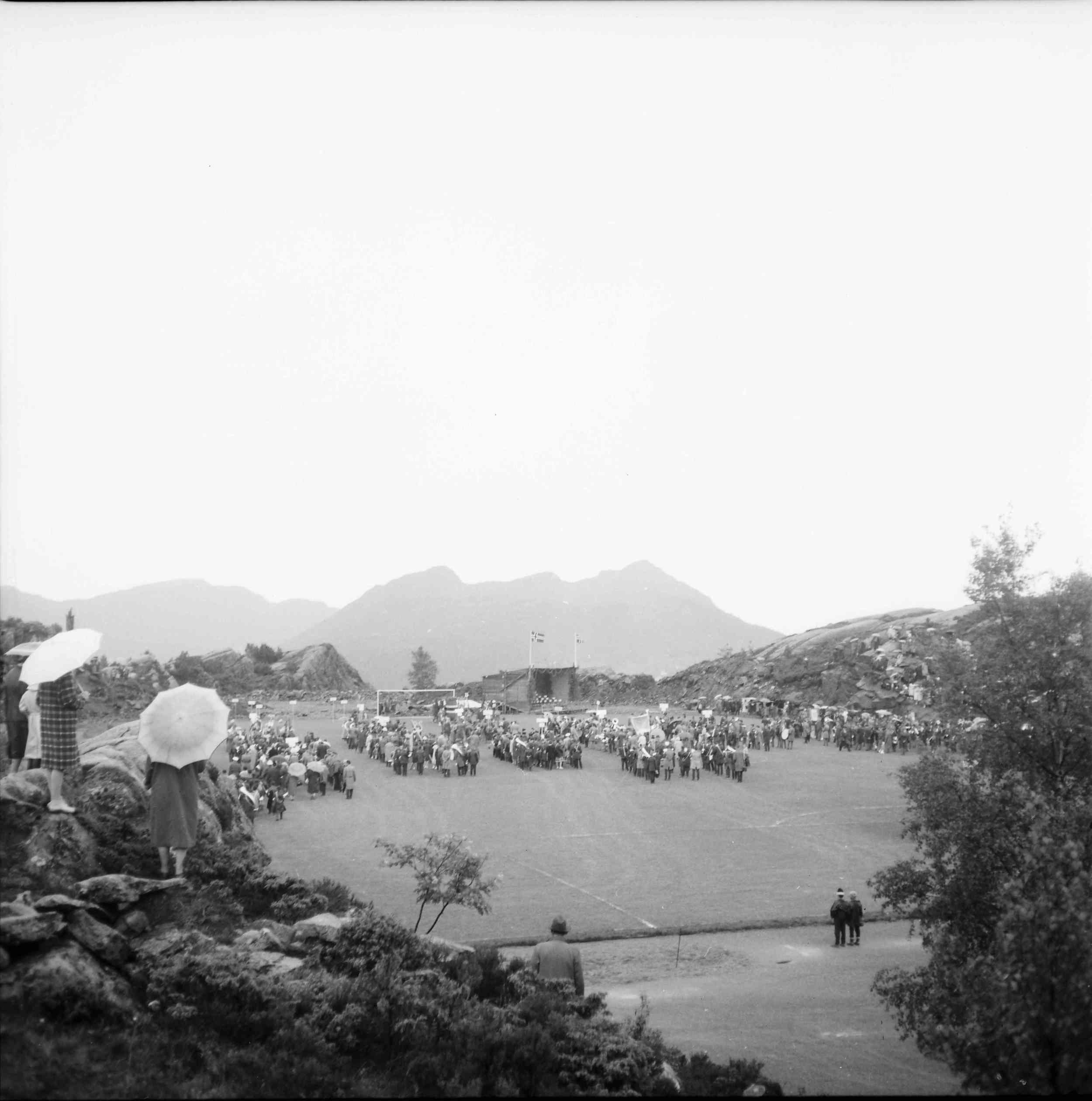 Korpsene er samlet på fotballbanen. Dessverre var ikke været særlig bra denne dagen (som man kan se av paraplybruken!).