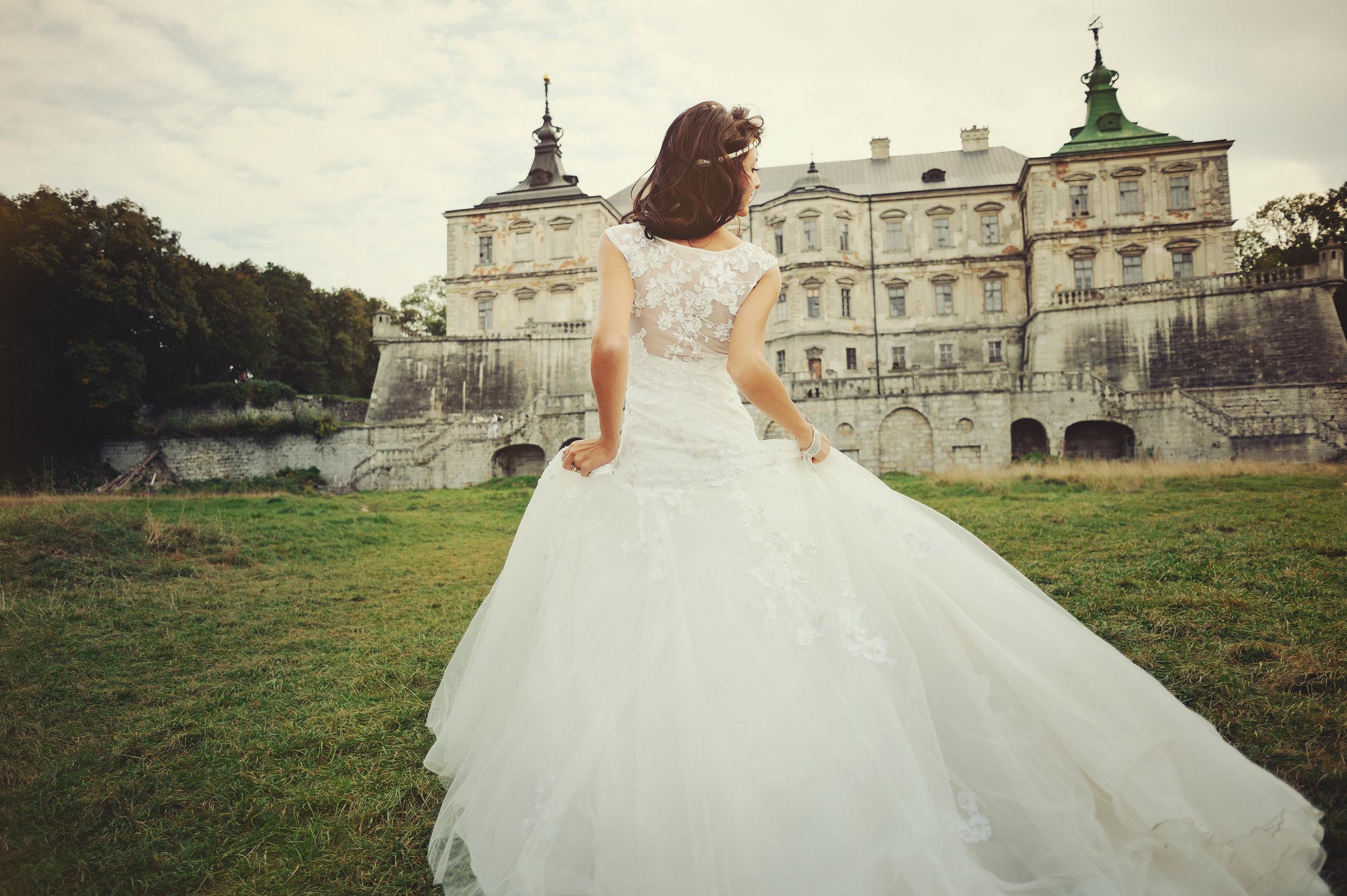gorgeous  bride walking next to castle
