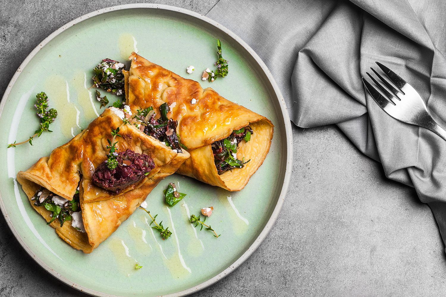 Olive oil egg roll w seasonal greens, feta and black olive tapenade. Recipe and styling by  Cle-ann , photo by  Hugh Adams .