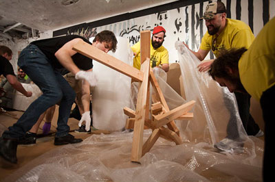 Gary Cullen (center) and his team The King of Cleats compete in the  wrapping portion of the Art Handling Olympics in New York (photo by  Michael Nagle for The New York Times)