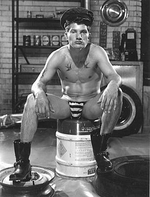 Bob Mizer . Untitled [Dennis Lavia Seated in Garage], 1964