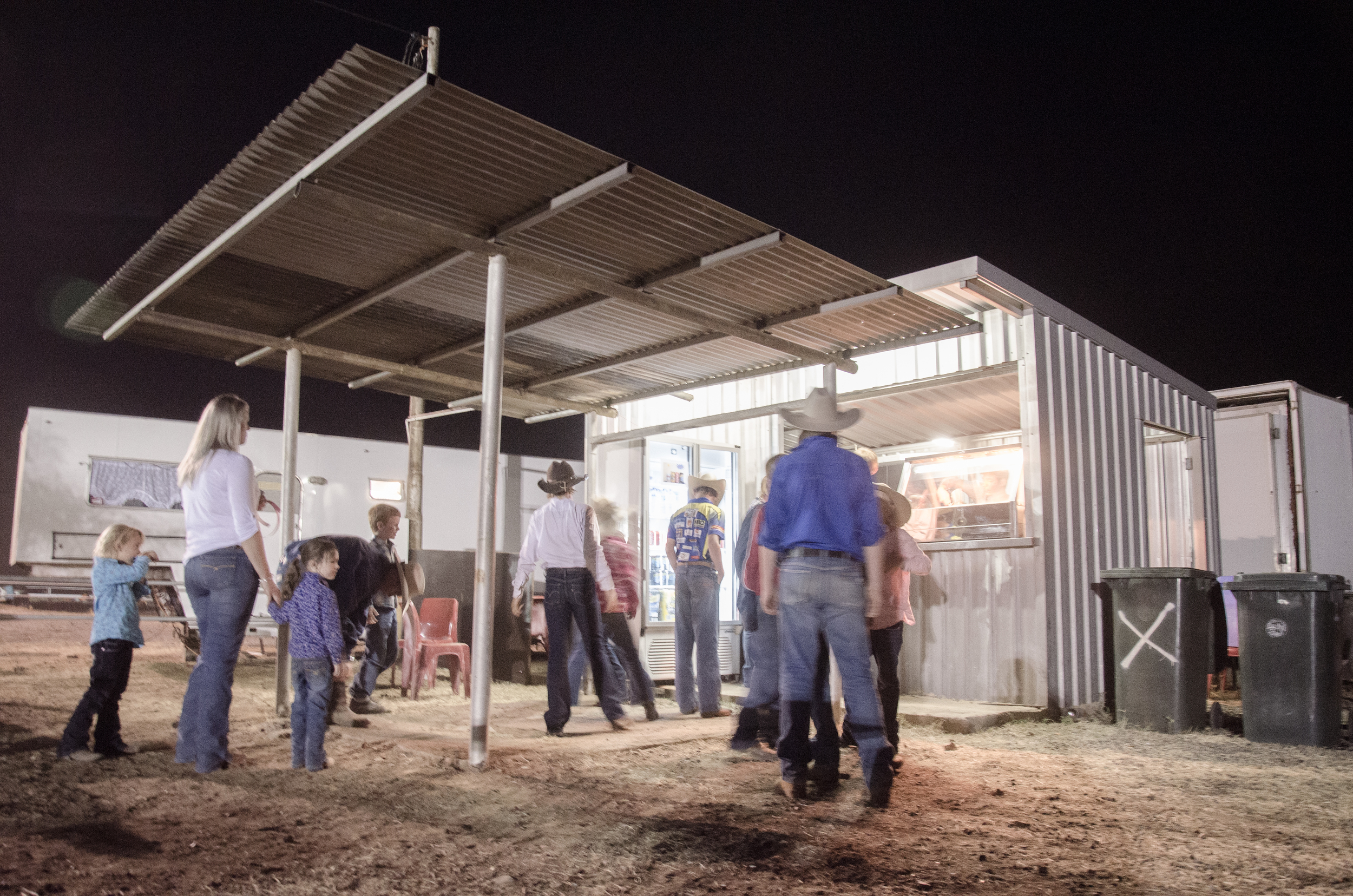 People get in line for a bite to eat before the night campdraft rodeo competition in the Australian heartland.