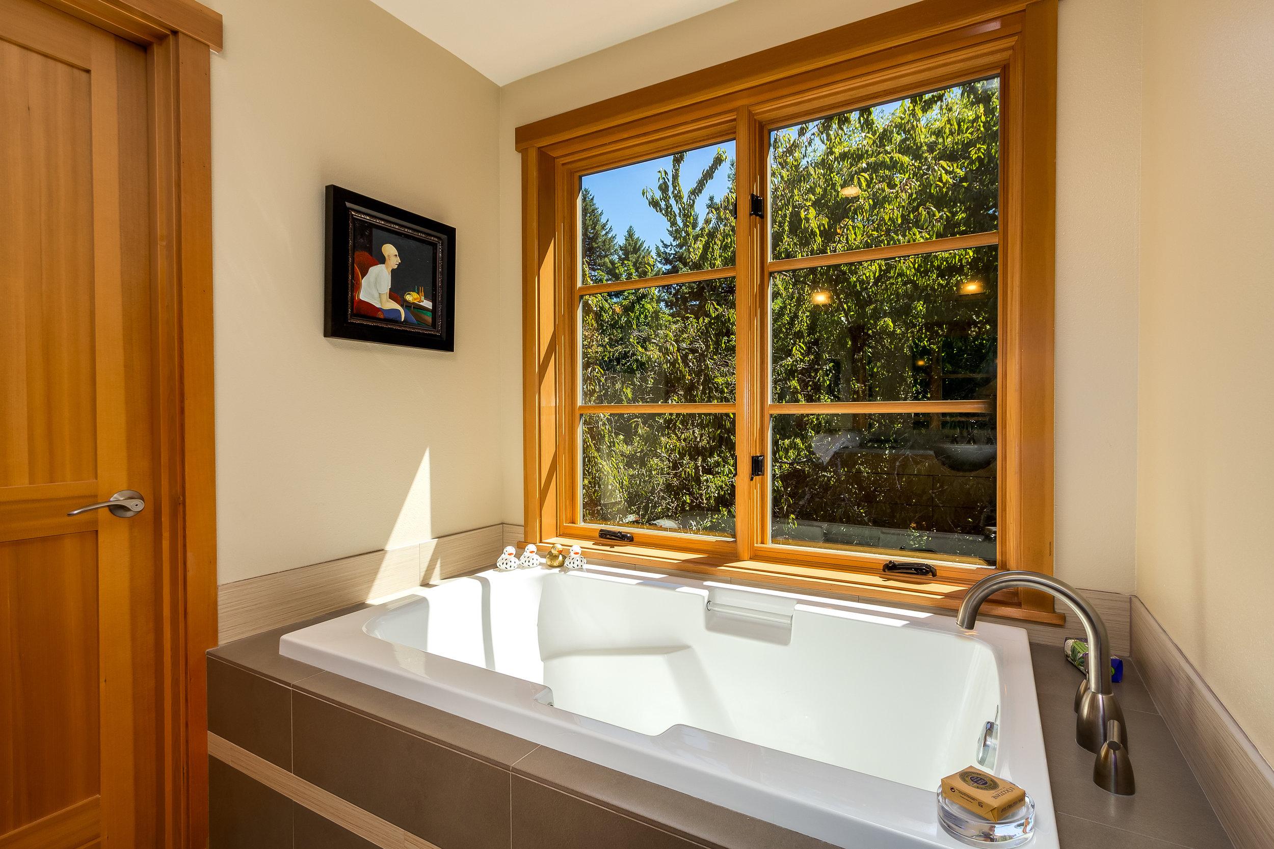 Master Bath soaking tub overlooks the lush landscaping.