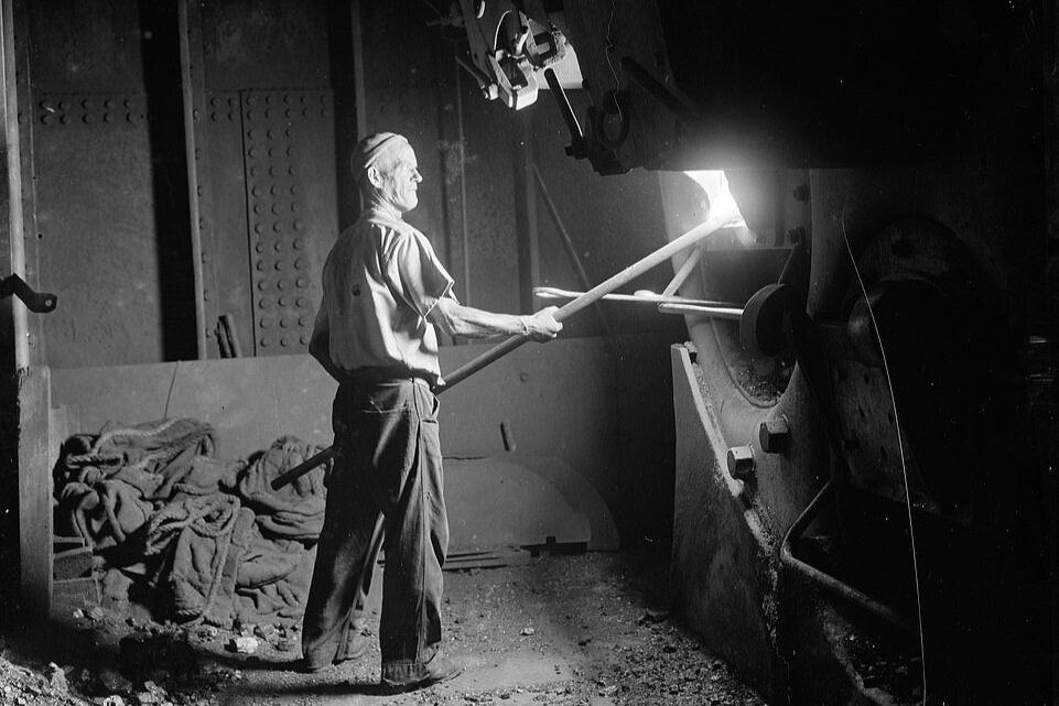 SS Eston's stoker raking the coal fires in the ships boiler