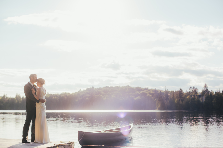 Bride & Groom by a canoe on the lake by Sainte-Marguerite-du-Lac-Masson Wedding Photographer