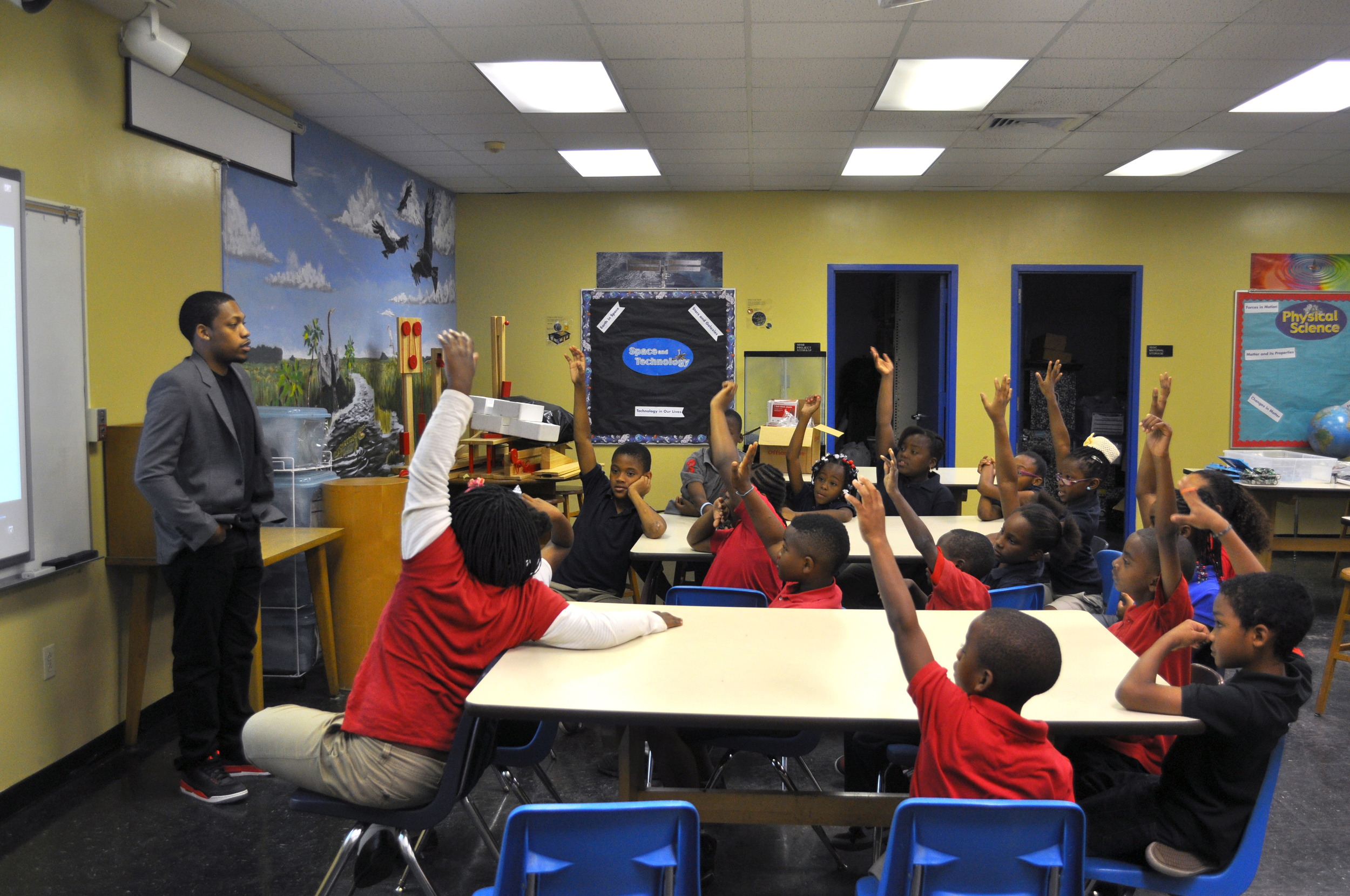 """3rd graders at Rainbow Park Elementary eagerly answer Germane's question, """"What does an architect do?"""" at Career Day."""