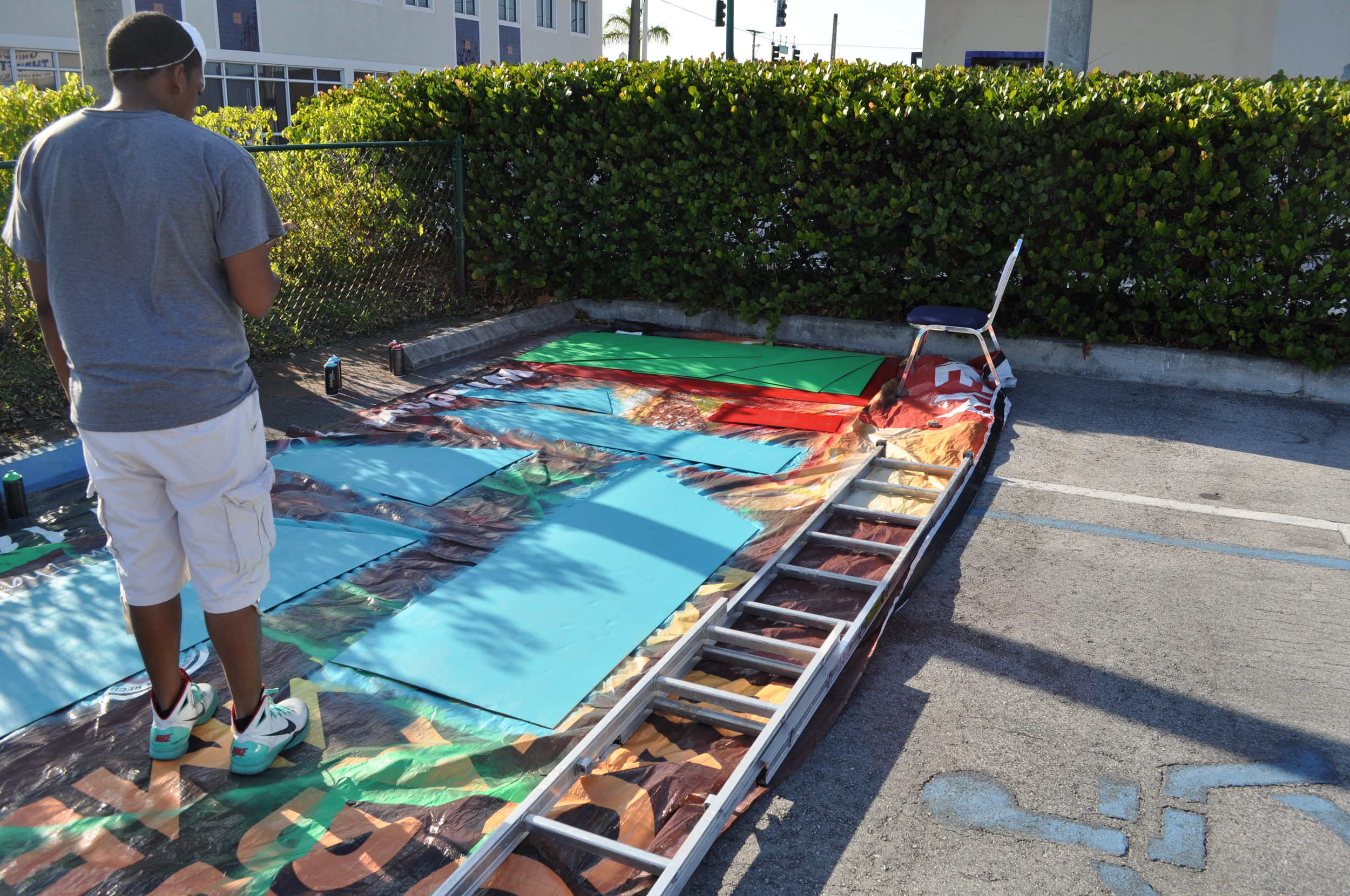 Germane spray paints the cardboard for tomorrow's Pop-Up Park before the sunsets.