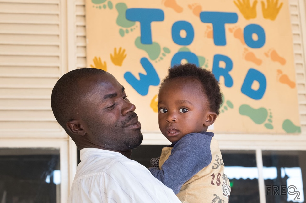 © Peter Casamento Photography/FREO2  A father waits with his son, outside the busy Toto Ward, for a doctor's appointment. Toto and Mtoto means 'child' in Swahili.