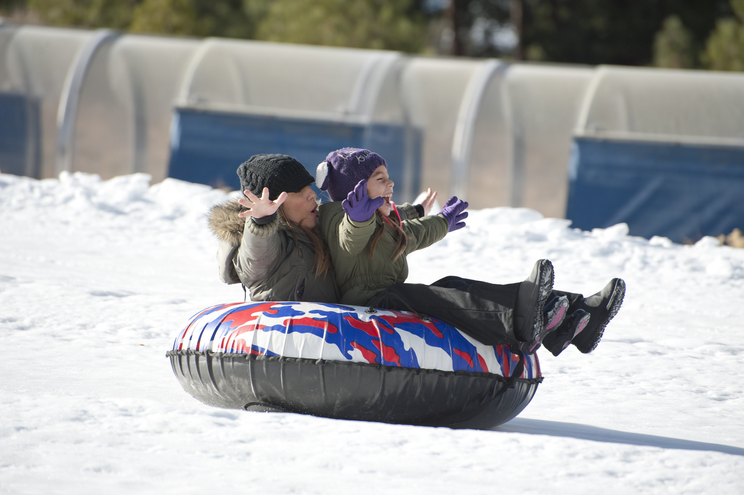 A mother and daughter race down the snowy hill at Big Bear Snow Play Nov. 19, 2016.