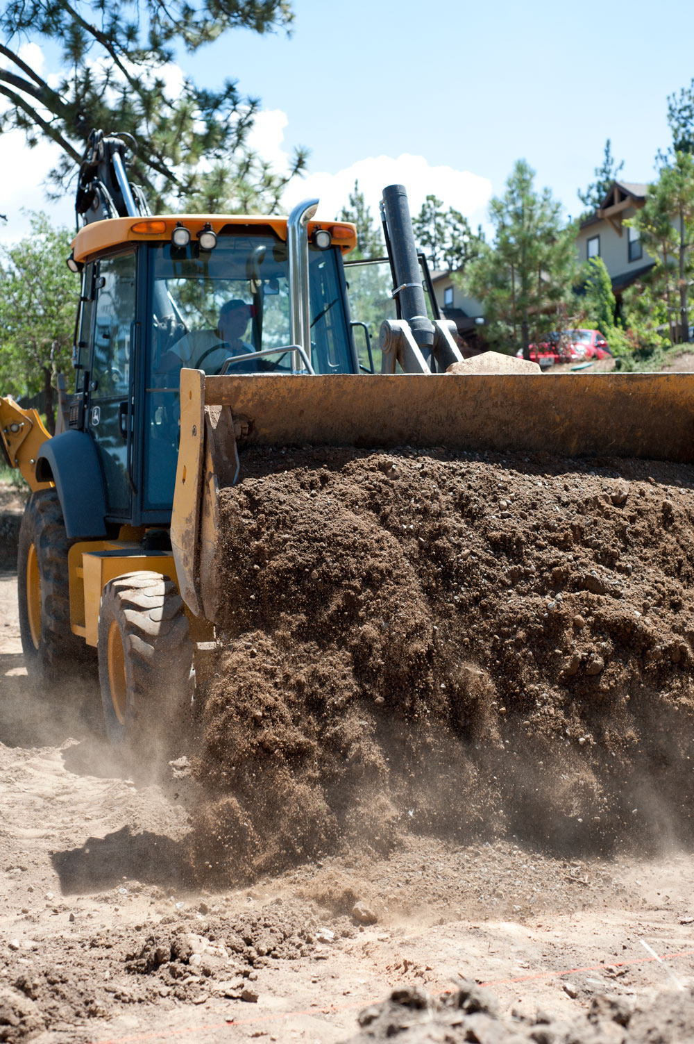 A construction worker operates a backhoe loader on one of the soon-to-be parking lots off Pennsylvania Avenue in Big Bear Lake Aug. 5, 2016.