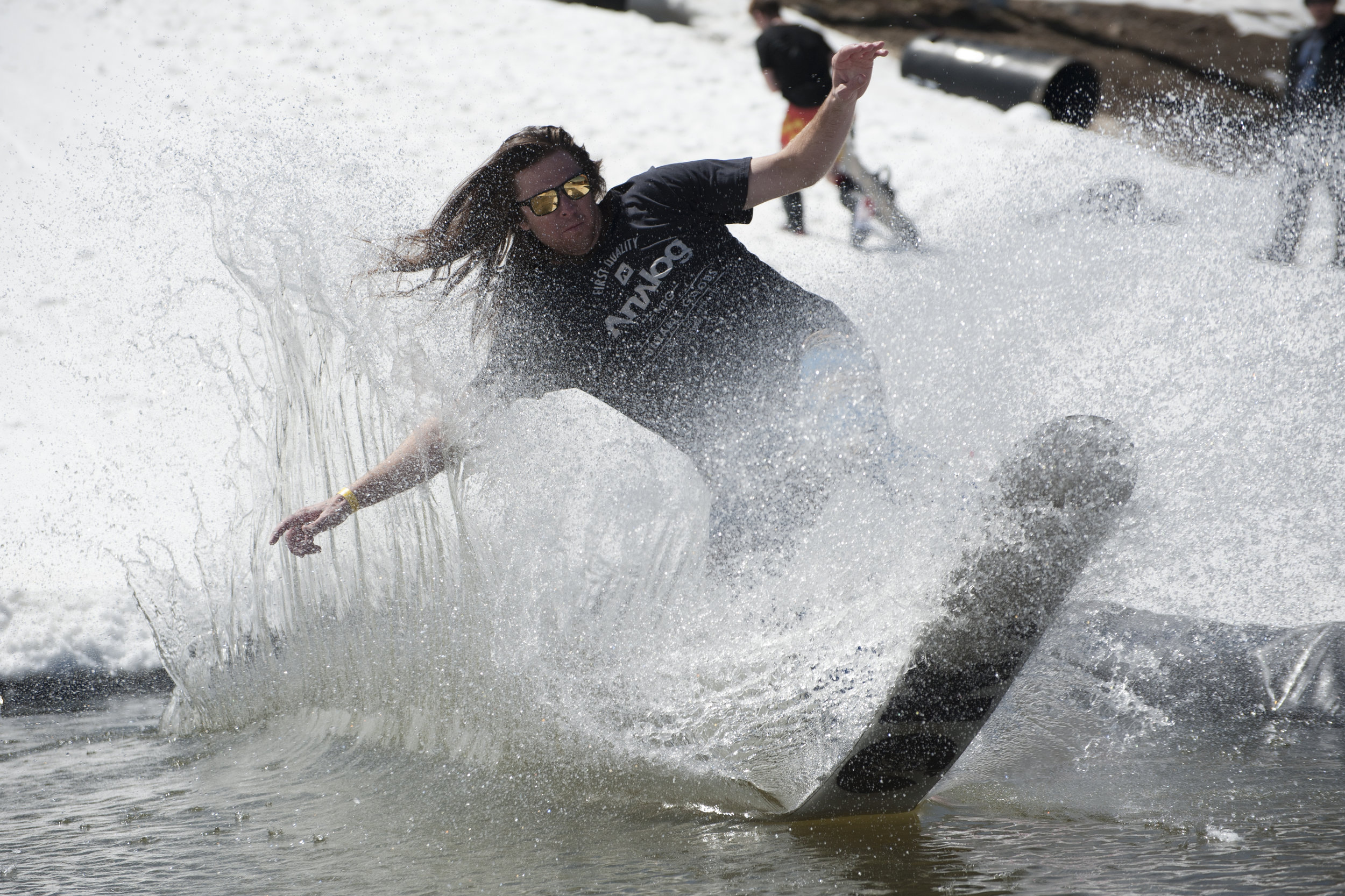 A snowboarder skids across the water during the pond skimming event at Bear Break March 30, 2017. Bear Mountain's annual spring break event hosts a variety of competitions throughout the week.