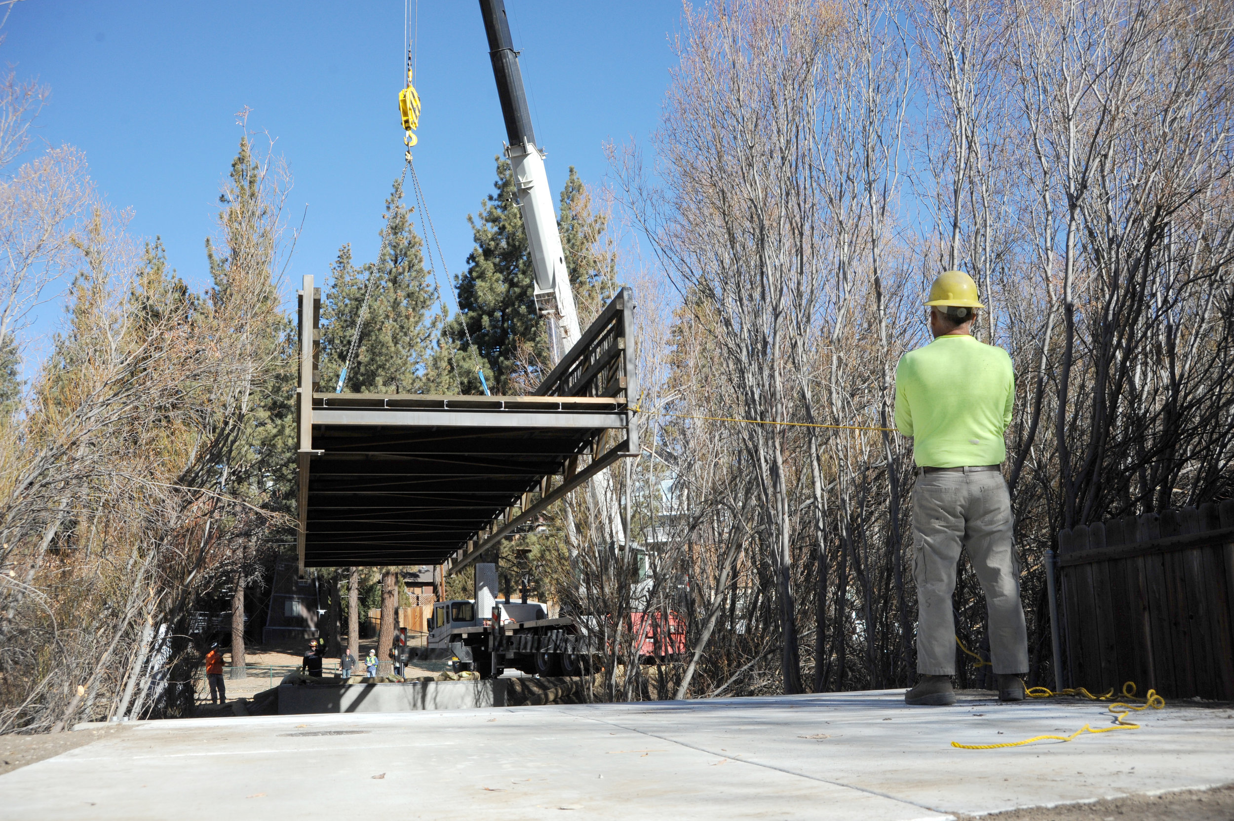 Gustavo Marquez, right, helps guide a 25,000-pound bridge over Rathbun Creek Dec. 15, 2017. The city of Big Bear Lake installed the 64-foot bridge to connect two existing segments of Rathbun Creek Trail.