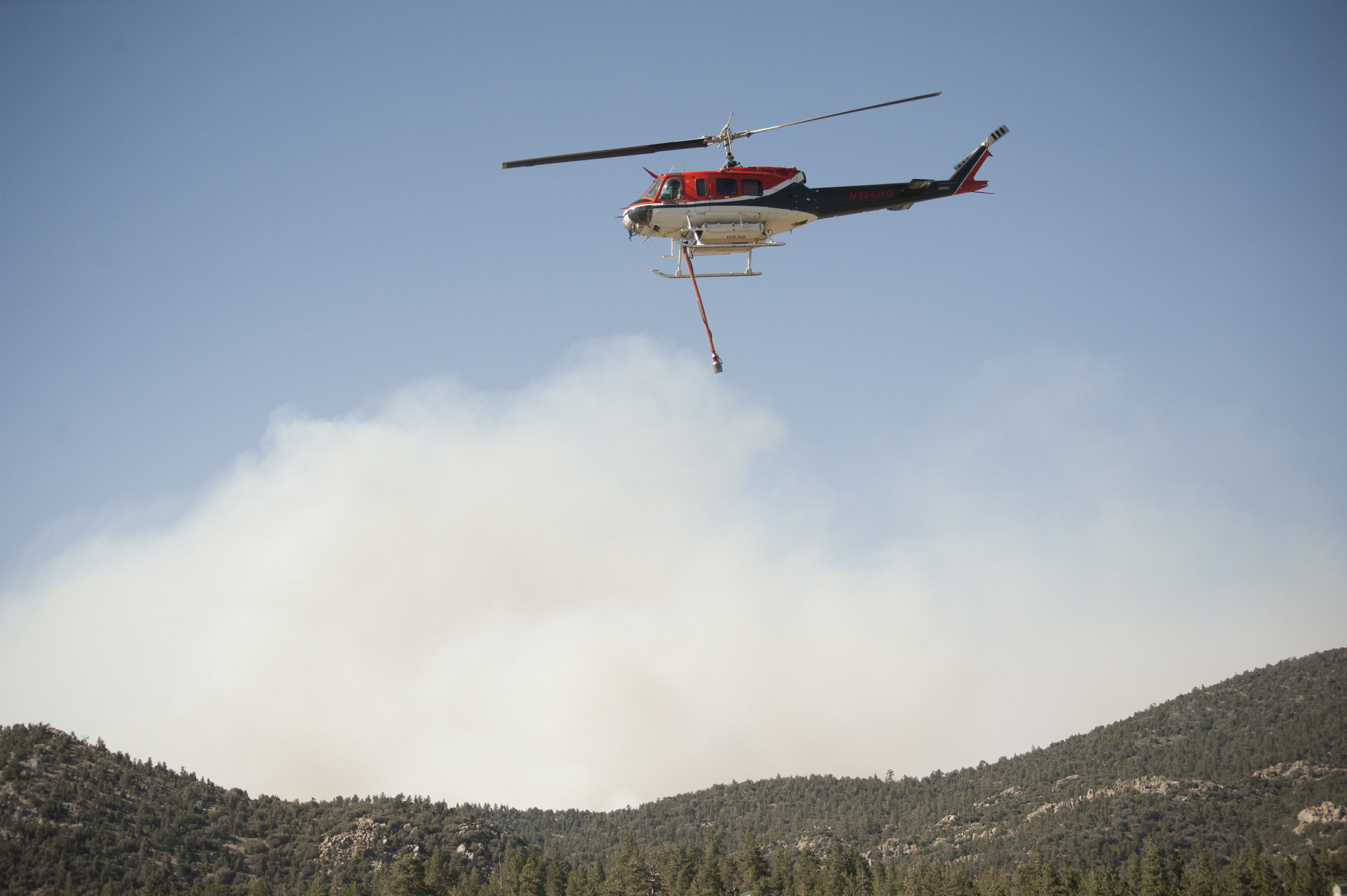 A helicopter heads past smoky mountains toward the lake to refill during the Holcomb Fire June 20, 2017.