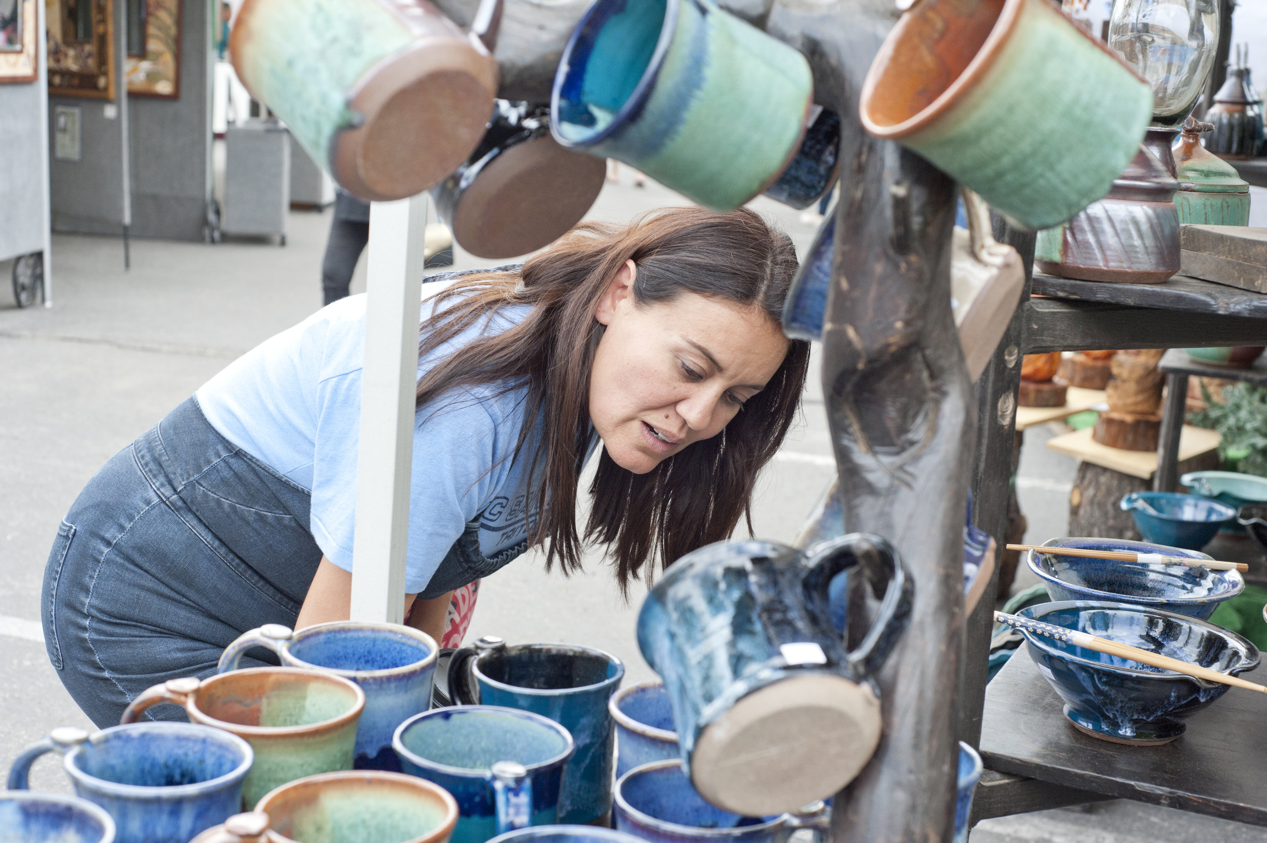A woman checks out the many works at the Fabrile Studios Pottery stand during the Art on the Lake art show in Big Bear Lake Aug. 20, 2016.