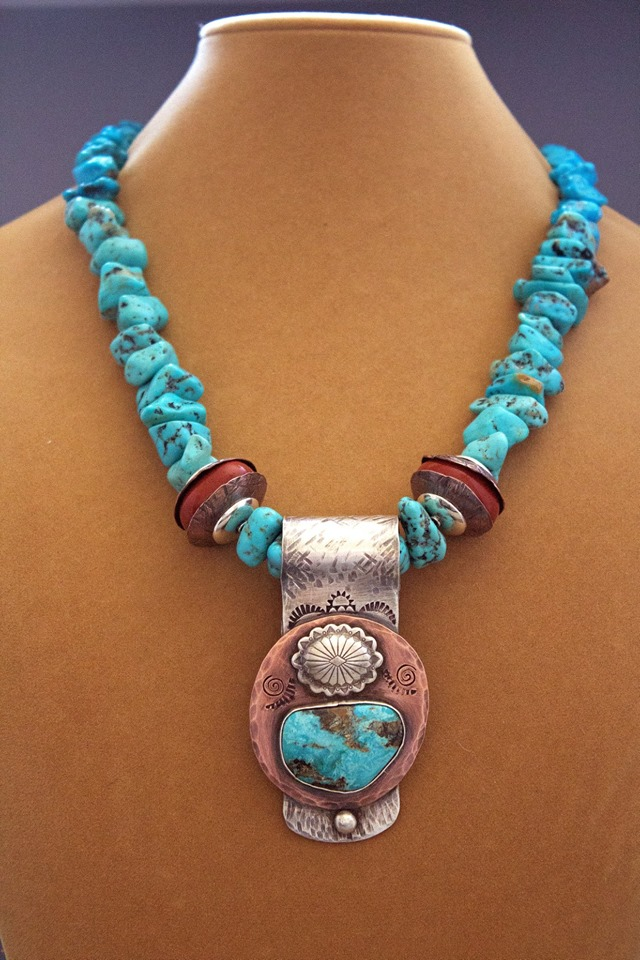 """- This stunning sterling silver and 100% copper work of wearable art features outstanding turquoise from mines in both Arizona and Nevada. Enhanced with handmade copper bead caps and silver, the pendant measures 3"""" x 1½"""" and drops from 18 inches of chunky turquoise stones."""