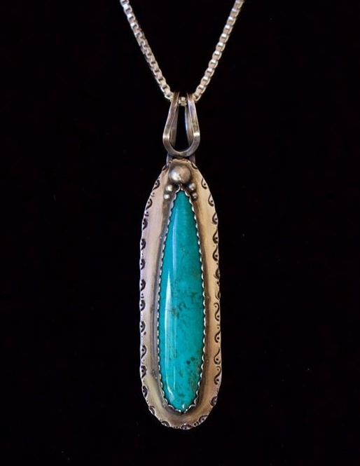 "The Wonder Of It All"" Pendant – classic with a little Southwest Twist featuring a gorgeous Kingman Turquoise stone cut by Jason Brousseau, NM and set in sterling silver elicited the following from  Fronnie Bealer ~ ""You are walking along in the desert leaving some footprint (the little scrolls on the sides) when you serendipitously come upon a narrow lake, which offers refreshment for body and soul. I love the splash of turquoise."""