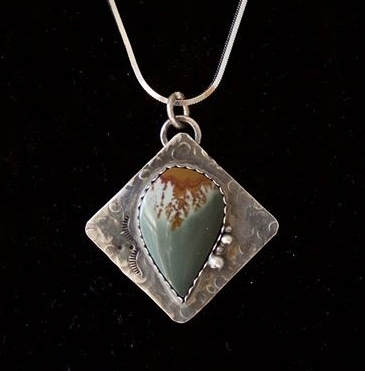 """Owyhee Desert Summer"" features an Owyhee Jasper cut by Jeff Hansen, AZ and set in sterling silver elicited this from  Denise Jansky ~ ""Looks liked brown lava flowing across white sand in to a blue/green ocean."" And this from Candace Gates ~ ""Truly beautiful, my pick so for, they are all beautiful though!"""