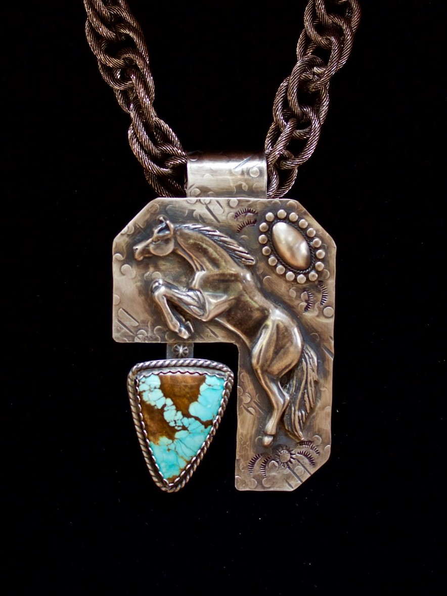 "- ""Unbridled"" is a large statement piece featuring an impressive Turquoise stone from the #8 Mine in Nevada shaped by Russ Kaniuth, Sunset Ridge Lapidary Arts, CA. The sterling silver pendant measures 3¾""h x 2¼""w and is highlighted with sterling silver accents – the horse was cast in a foundry in France."