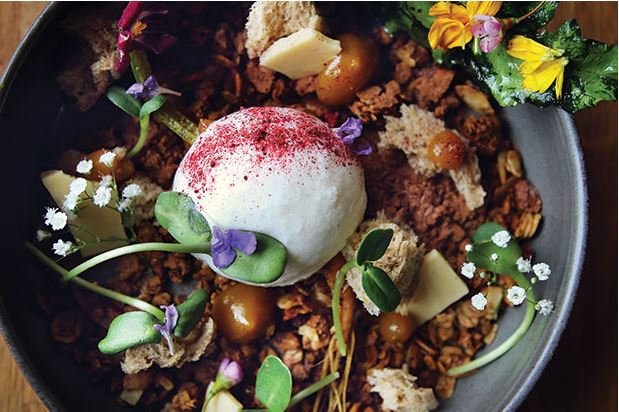 Coconut sorbet—made with the juices of mandarin and yellow beet, and sprinkled with house beet sugar—sits atop hazelnut and coffee cocoa granola, roasted white chocolate bark, hazelnut and fresh yeast sponge and candied baby beet greens from Eden Hill in Queen Anne