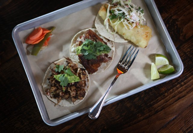 Super Bueno's tacos include, from left, vegetarian made with braised jackfruit, onions, garlic, chilies and guacamole; carne asada, with white onions, radish and cilantro; and fried cod, with cabbage, pico de gallo and cilantro. (Ellen M. Banner / The Seattle Times)