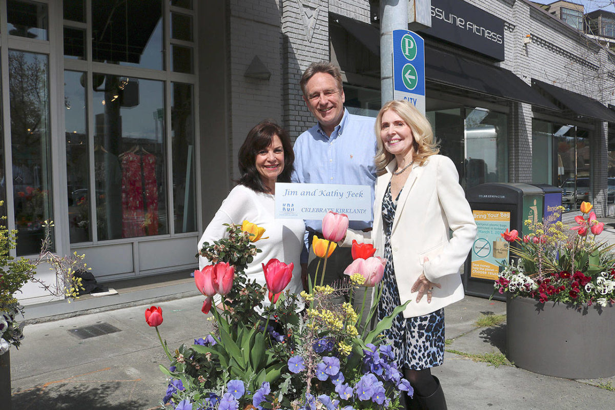 From left: Flower Pot program chair Anne Hess, KDA executive director Michael Friedline, and Flower Pot program chair Kathy Feek pose near flower pots in downtown Kirkland with a sample of the new plaques. Stephanie Quiroz/staff photo.