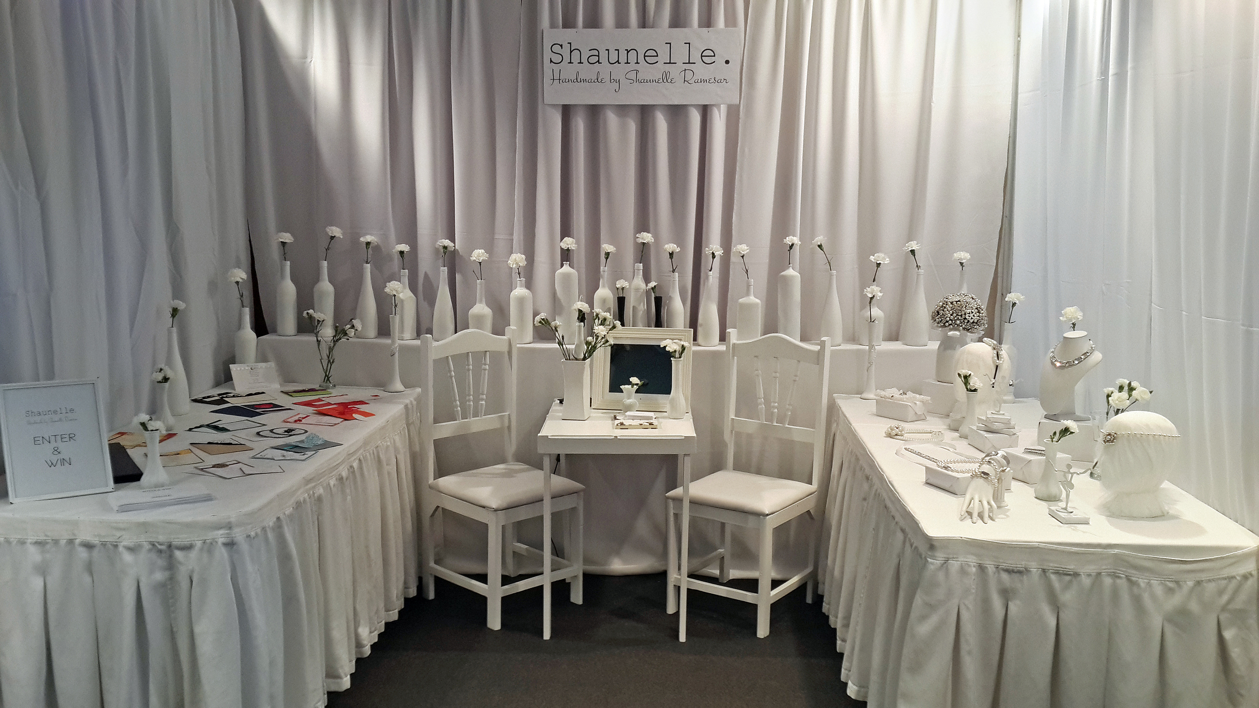 Shaunelle. Booth presentation details featuring a minimal all white design with fresh flowers accents. The space received an overwhelming response.