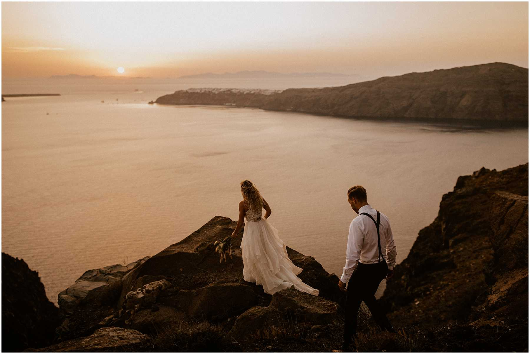 A couple adventuring at sunset after their wedding in Santorini