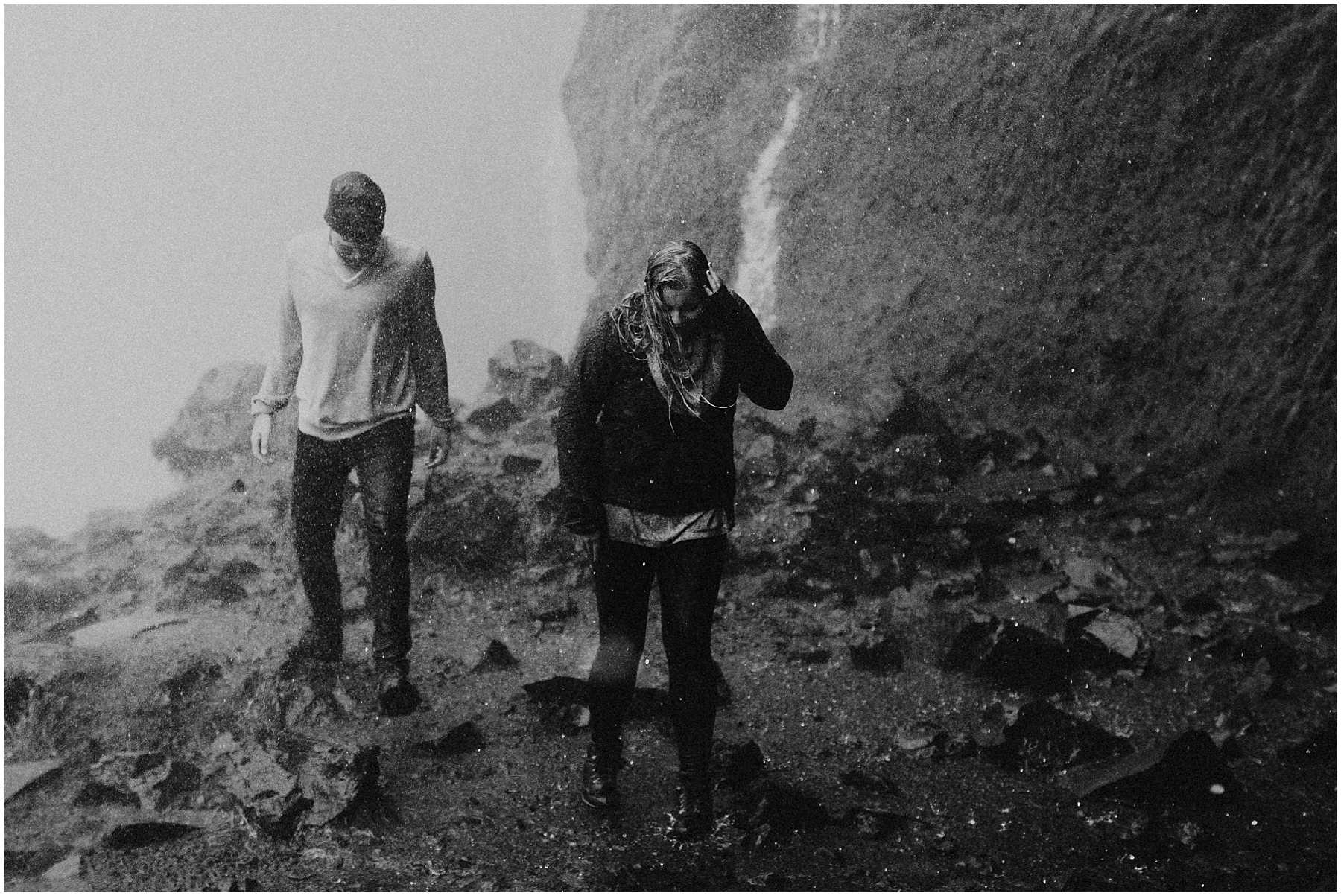 An adventurous couple soaked in a waterfall in Iceland