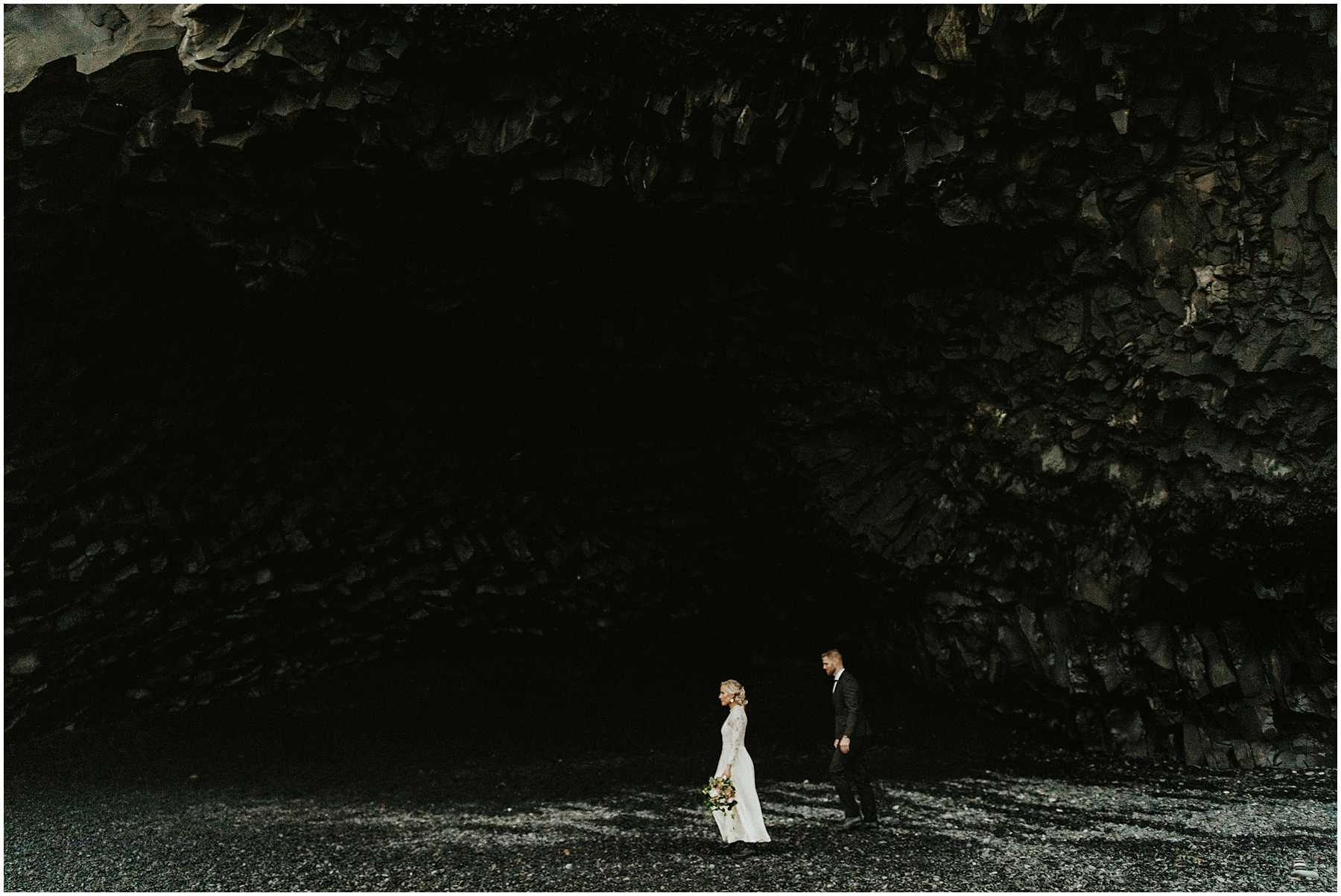 A bride and groom at Black Sands Beach in Vik, Iceland