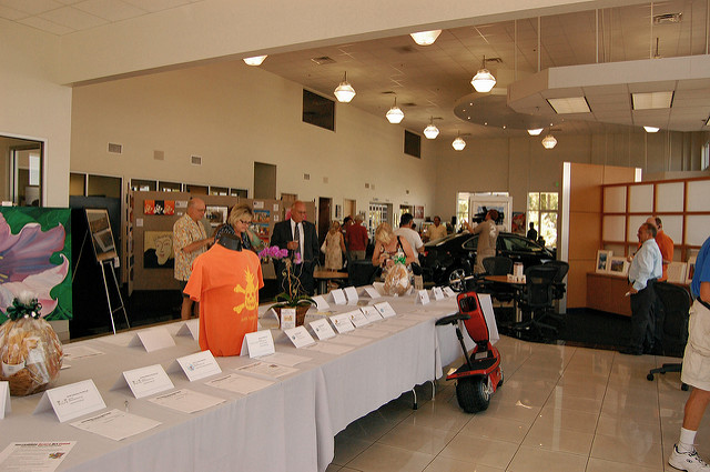 The silent auction table at the Incredible Acura Art Event, photograph courtesy of Stephan Cooke ( https://www.flickr.com/photos/aheram/3691107780 ).