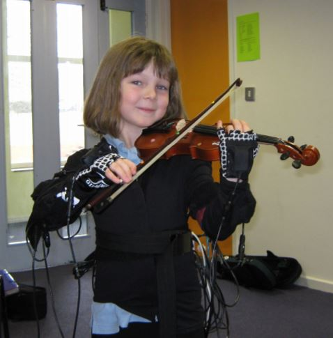 Fig. 2. A student learning violin using the MusicJacket  (Linden 535 ) (See  Buzzing to play: lessons learned from an in the wild study of real-time vibrotactile feedback )