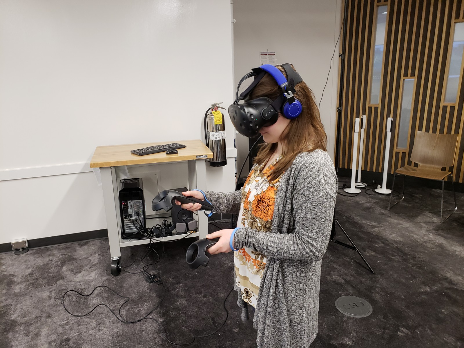 The full HTC Vive hehadset and controllers, which the author wears here, provides a fully immersive VR experience, but costs much more.  Photo Credit: Alyssa Wroblewski