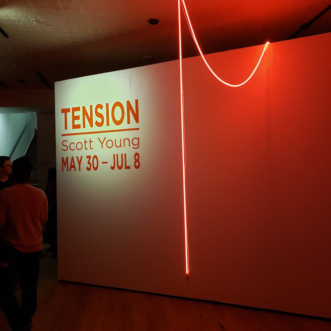 The entrance to Scott Young's Tension, which begins with a single string of warm neon light. Photo Credit: Alyssa Wroblewski