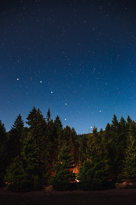 A campfire lights up the trees under the Big Dipper at Detroit Lake, Oregon