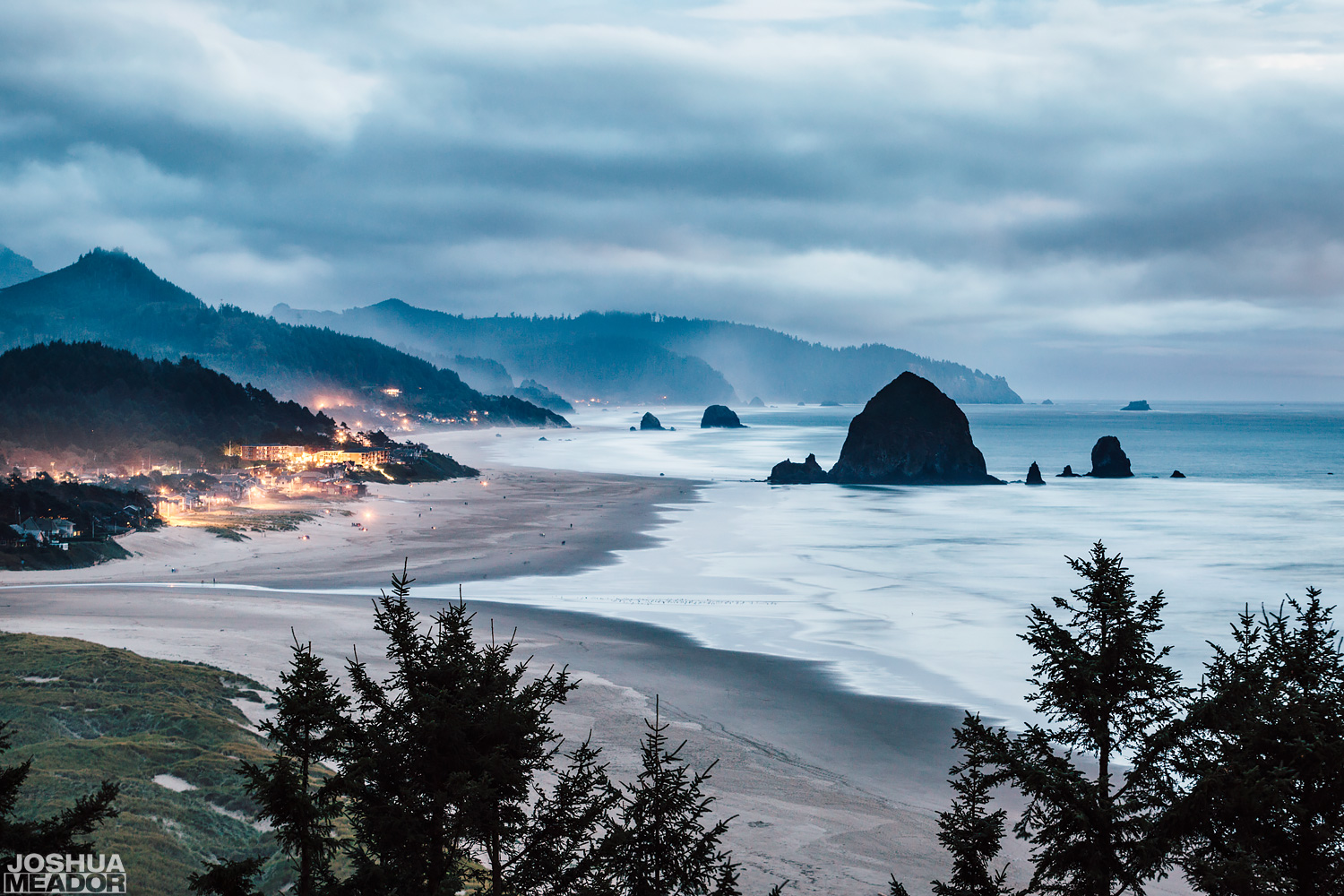 Fog and storm clouds above the mountains and Haystack Rock in Cannon Beach, Oregon. Taken from the edge of Ecola State Park