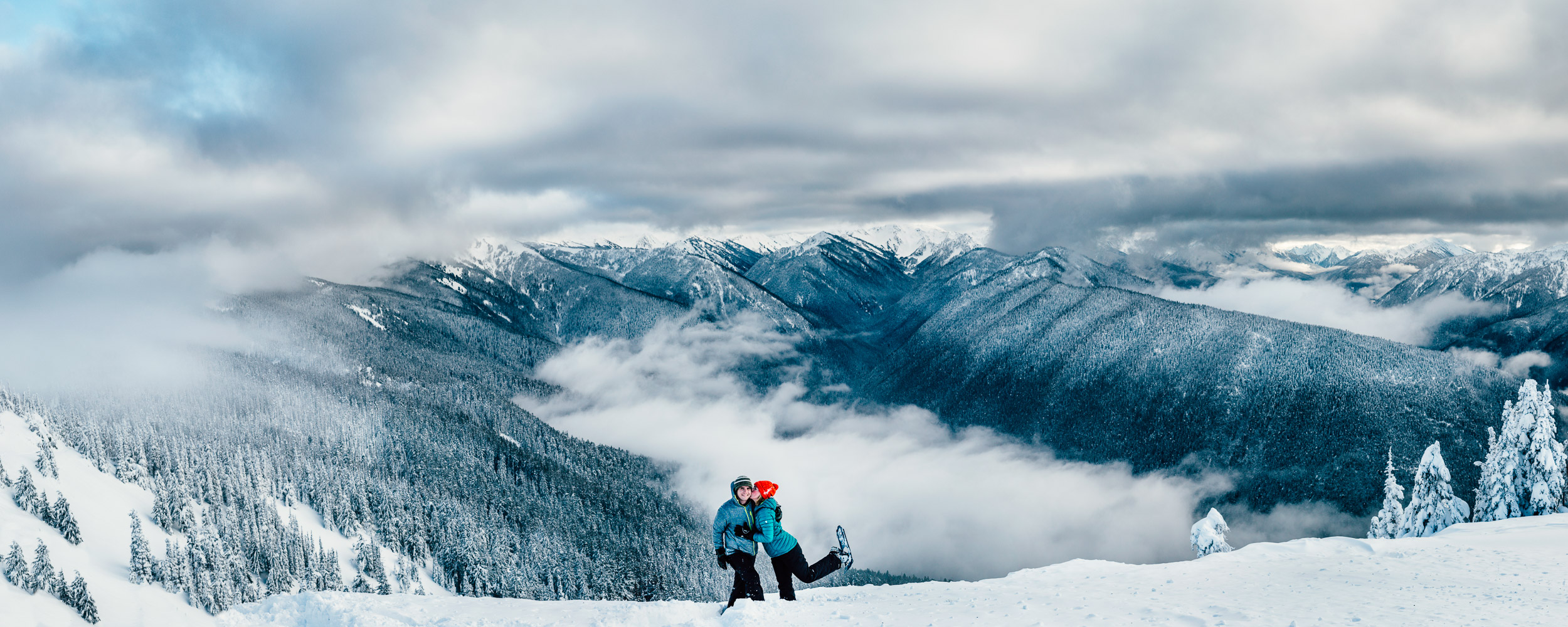 Snowshoeing couple in front of a building storm in the valley below Hurricane Ridge, Washington