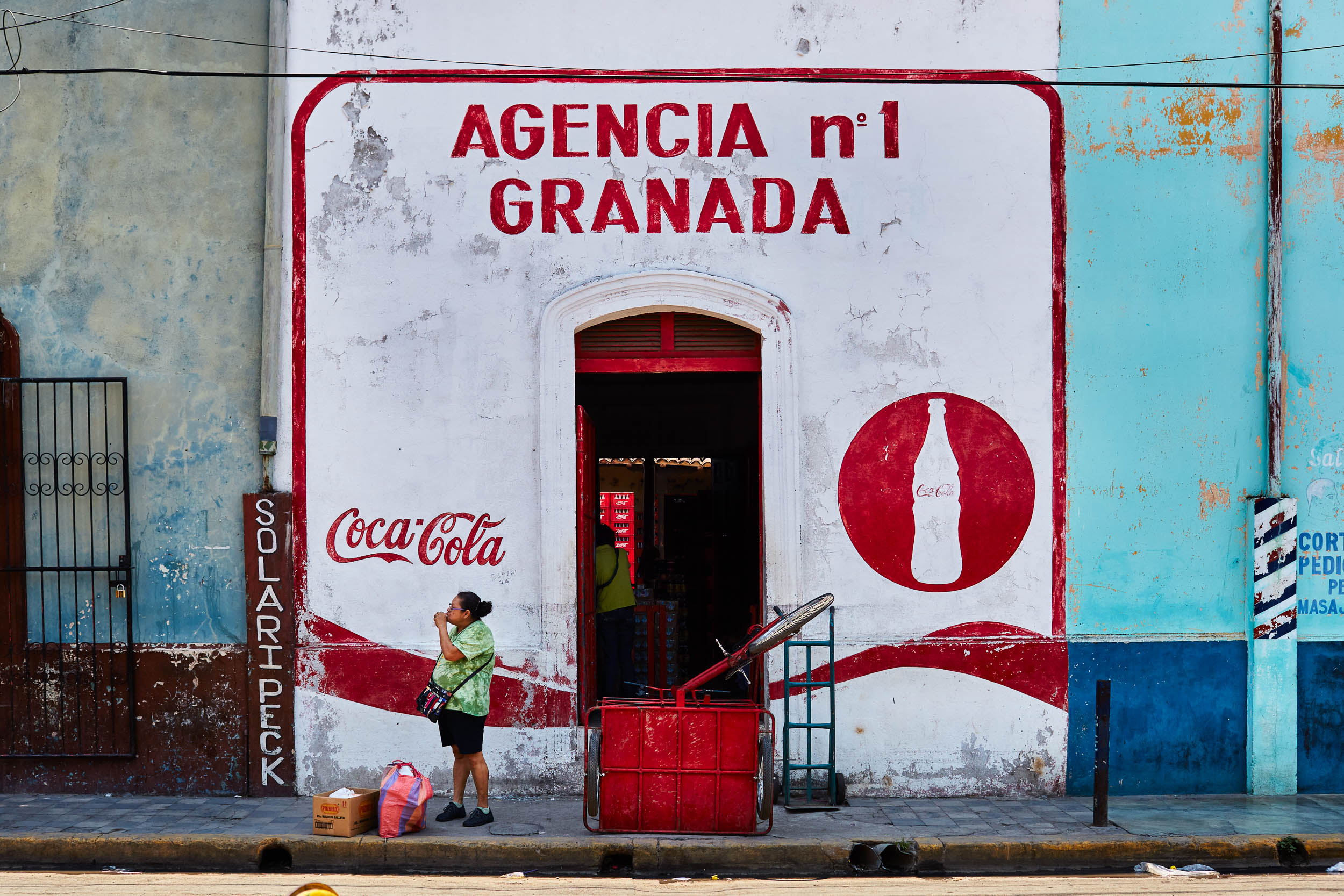 Woman standing outside a brightly colored store enjoying a cold drink on a hot day in Granada, Nicaragua.