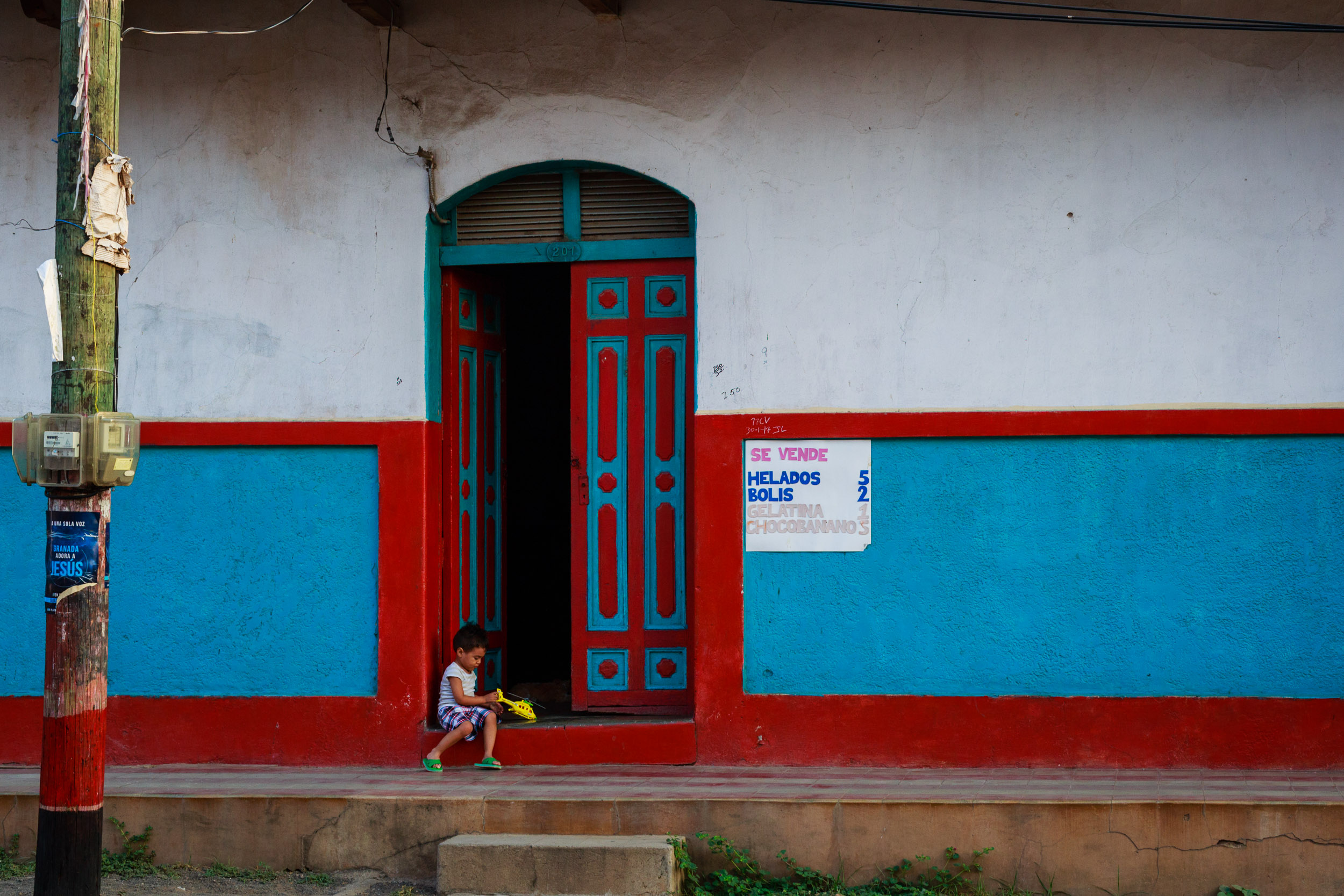 Young boy plays with a helicopter toy in his brightly colored house on a hot morning in Granada, Nicaragua.