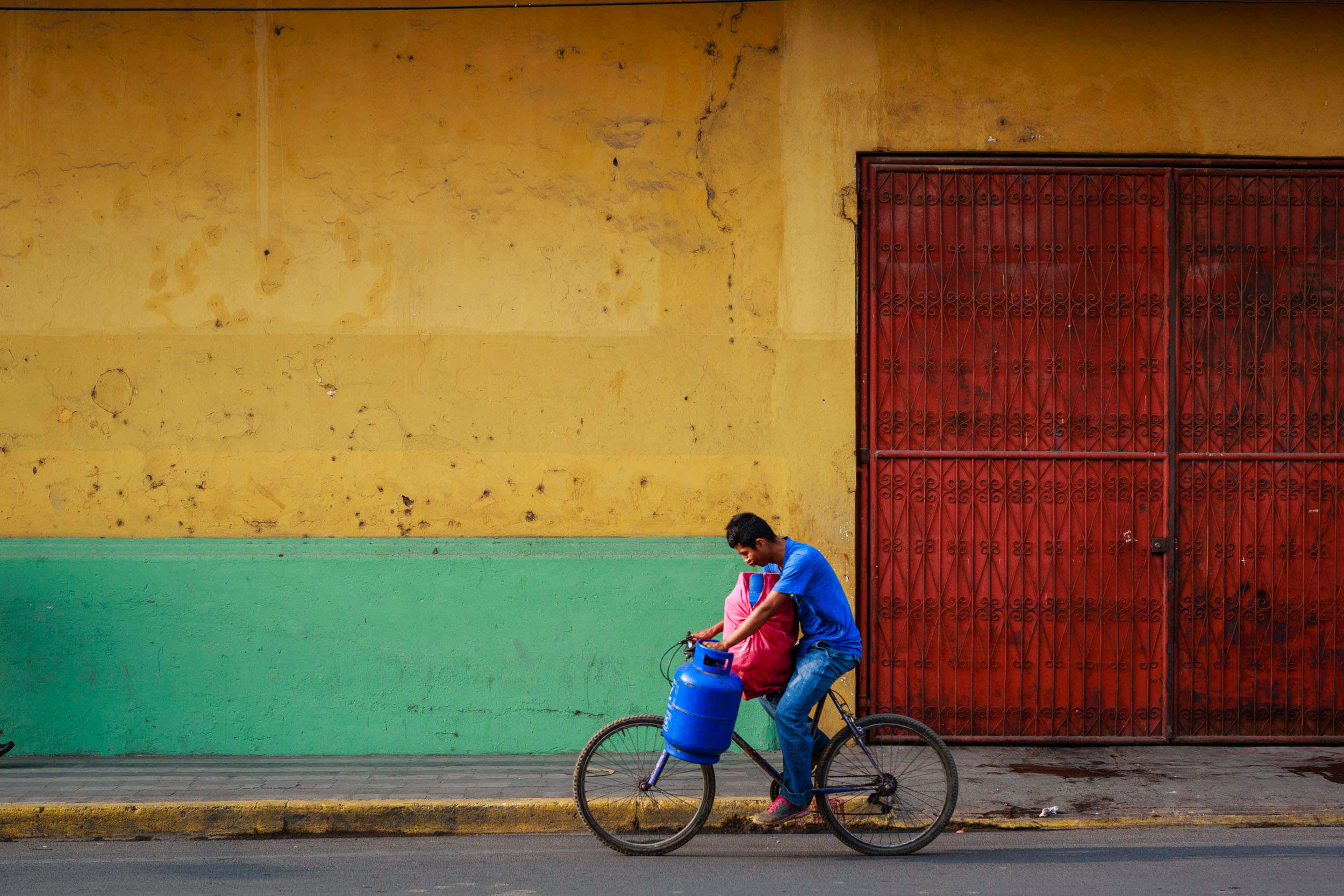 Man riding his bike along the colorful streets of Granada, Nicaragua while balancing 2 propane tanks.