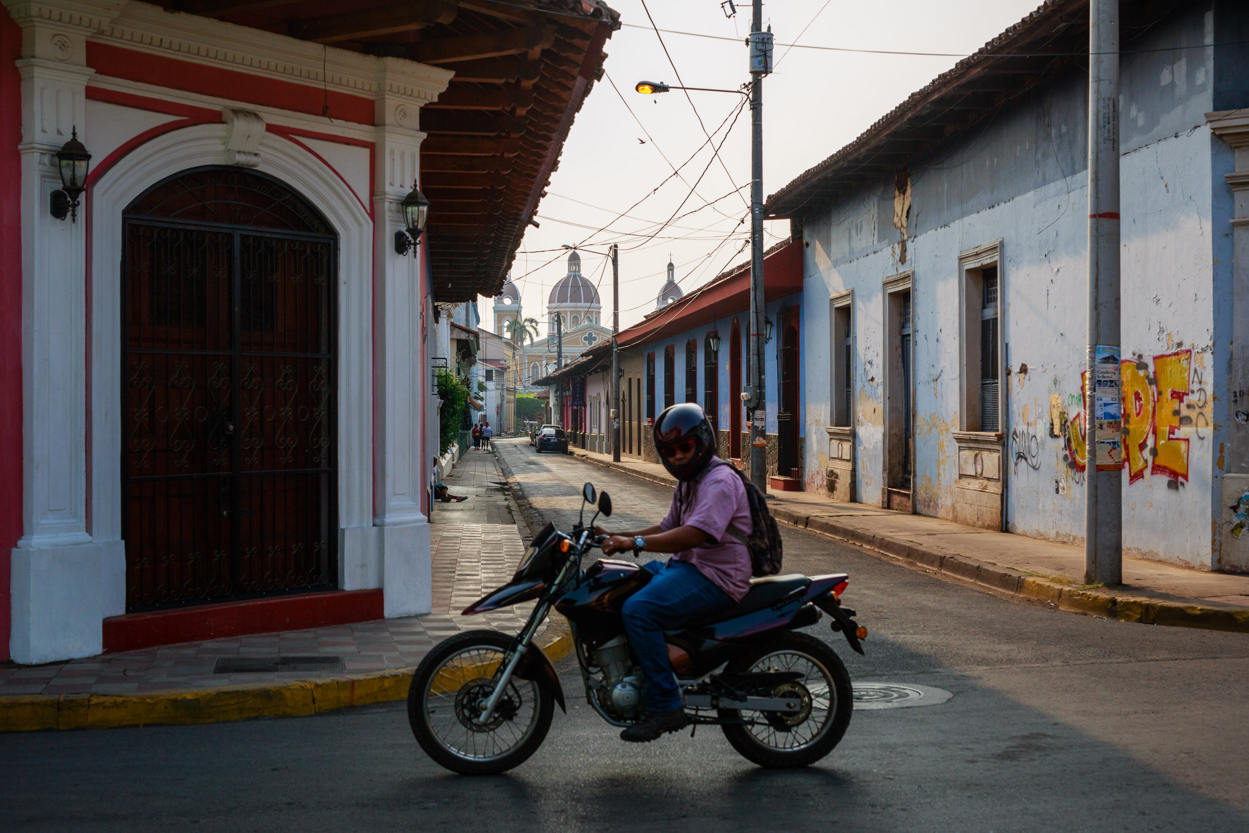 Man riding his motorcycle through the streets of Granada, Nicaragua
