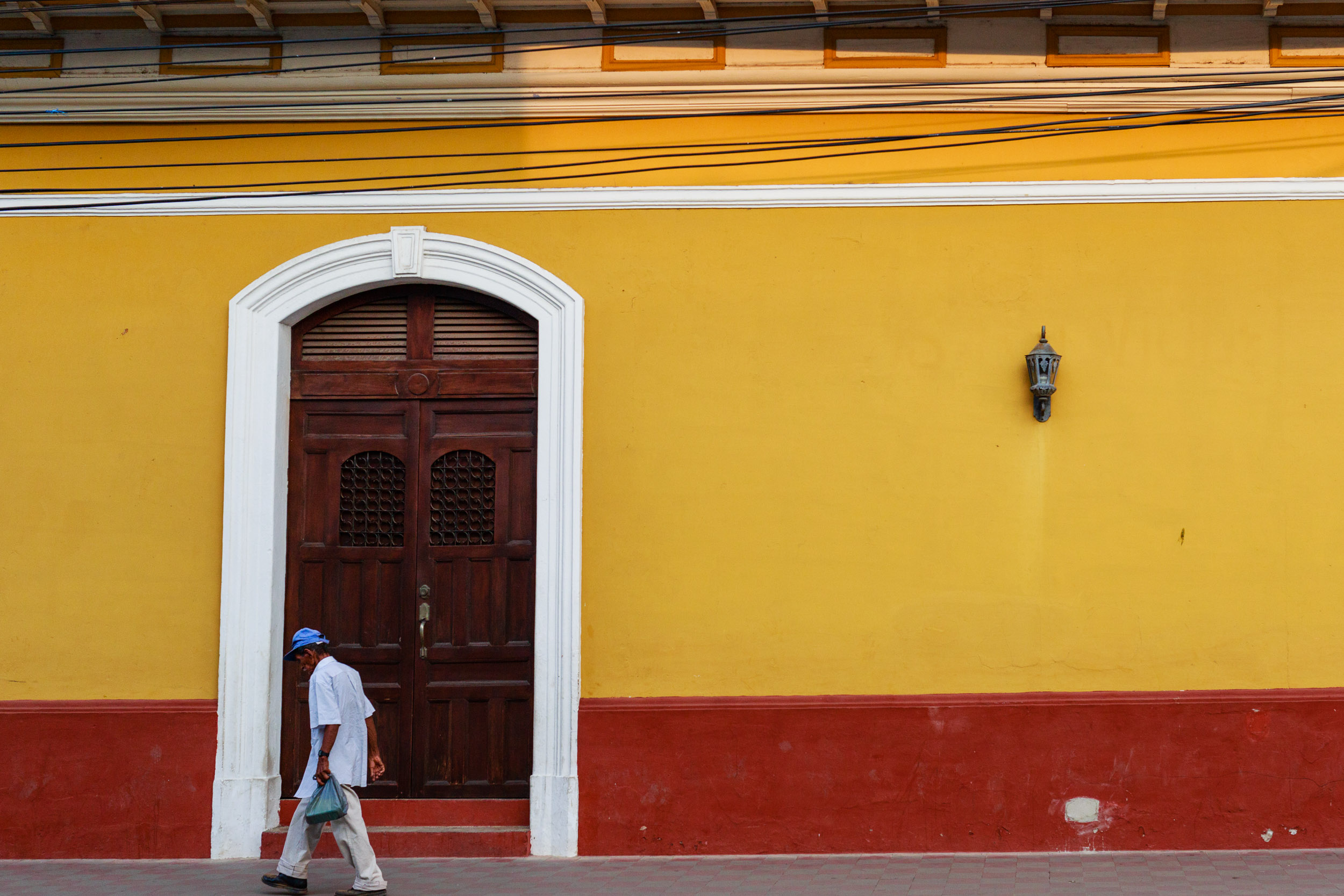 Old man walking along the colorful streets of Granada, Nicaragua after he got his morning groceries from the market.